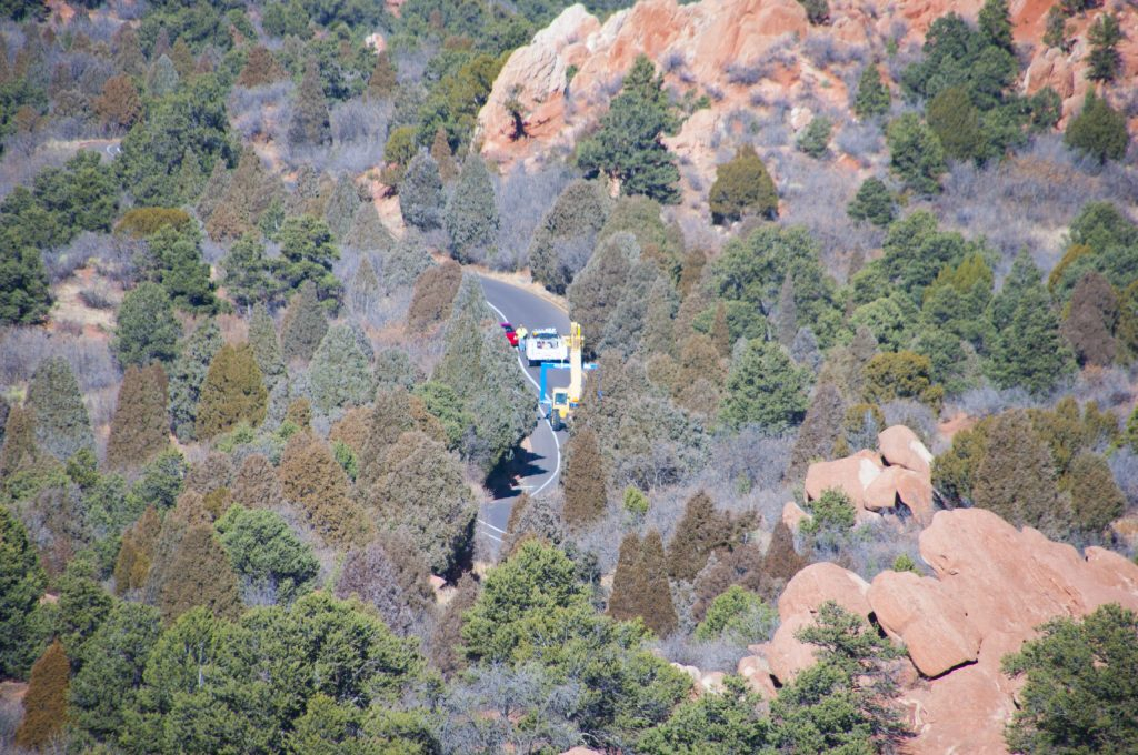 A crane transports the frame through Garden of the Gods park, as seen from the High Point Overlook parking lot.