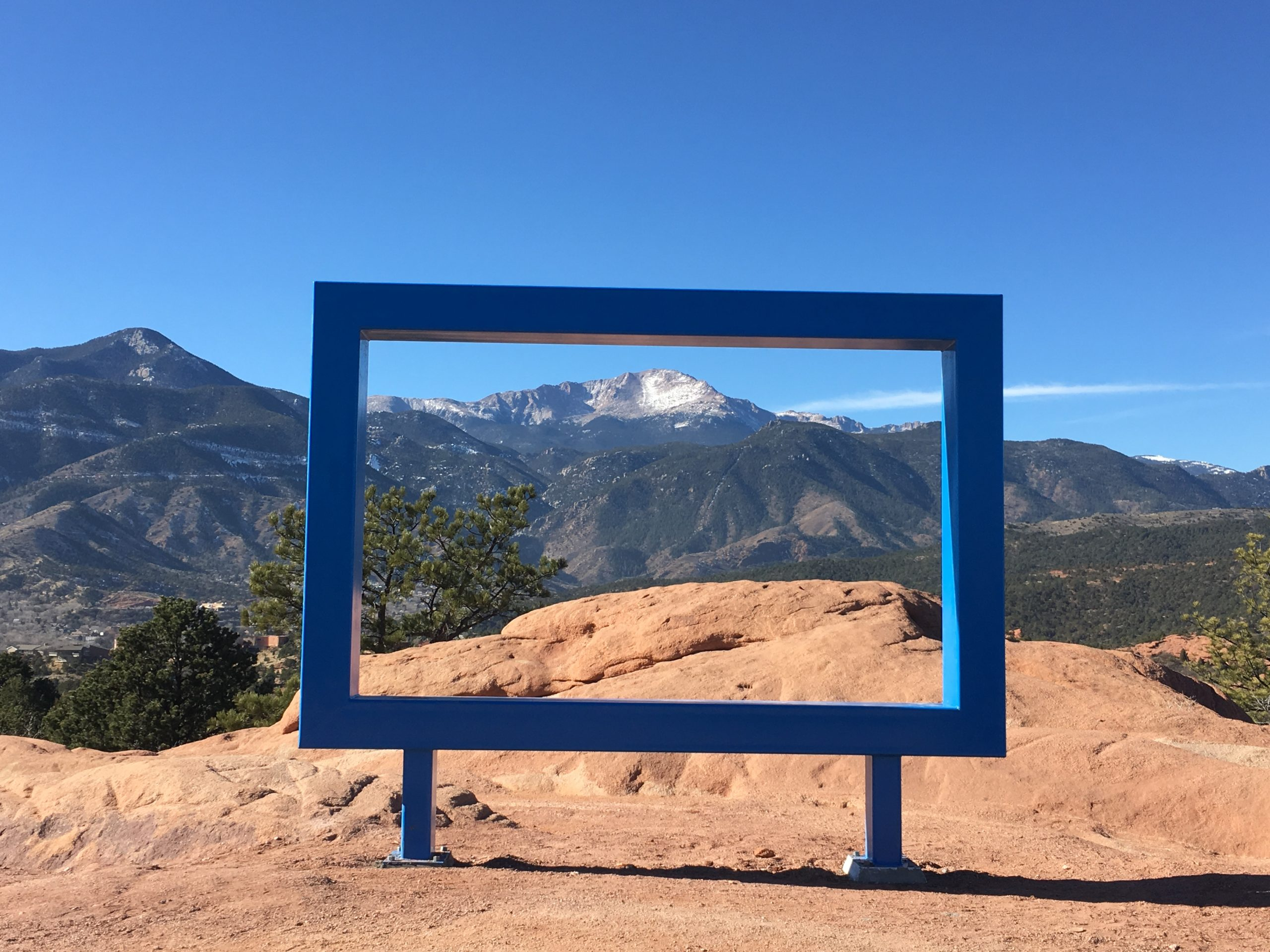The view through a newly-installed large metal frame at Garden of the Gods, taken from a crouched position at the edge of the High Point Overlook parking lot.