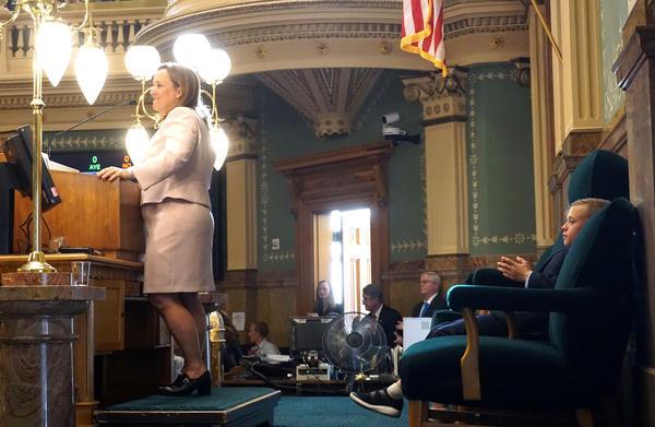 Colorado House Speaker KC Becker addresses lawmakers Friday morning as her son, Leo, applauds her speech.