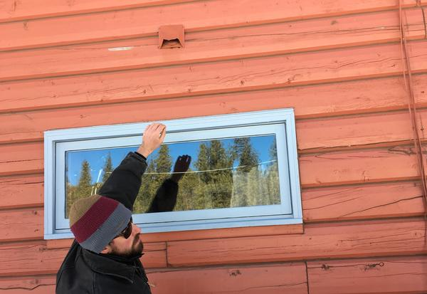 Wildfire mitigation specialist Ben Yellin searches a home in Boulder County for vulnerabilities, pointing to a vent where embers could get trapped.