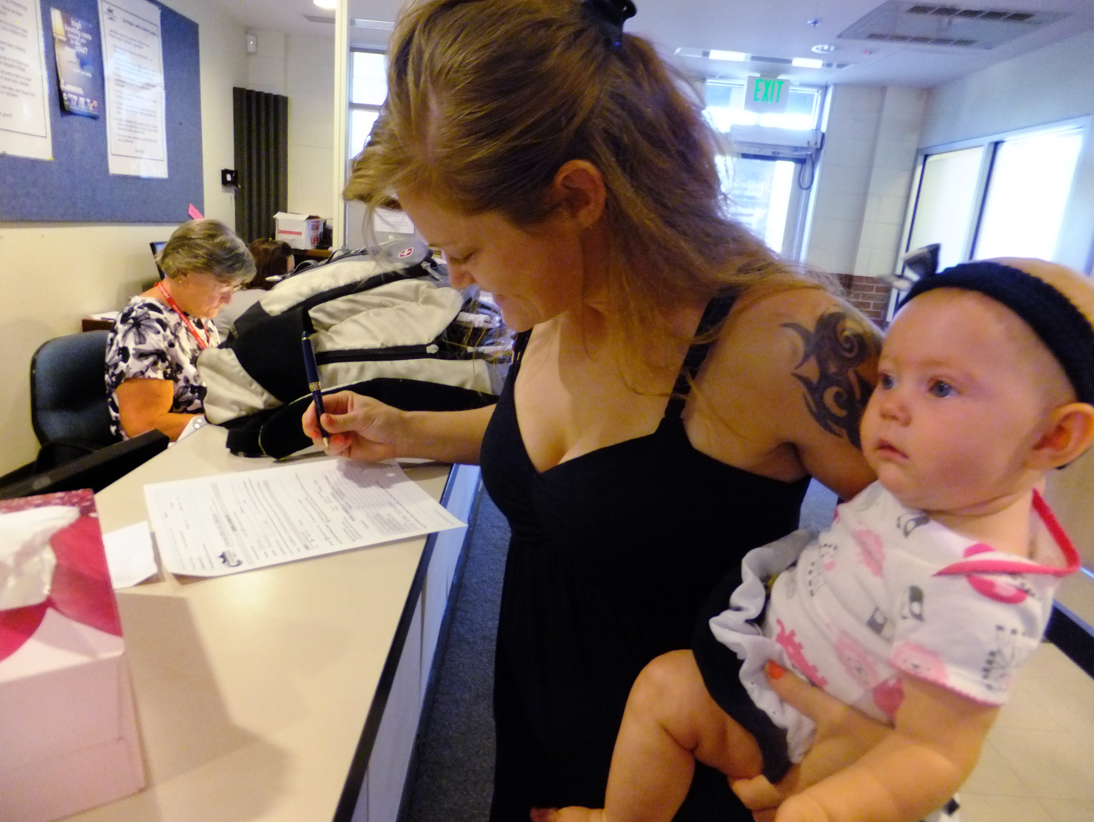 <p>In this July 16, 2012, photo, Laura Fritz, 27, left, with her daughter Adalade Goudeseune fills out a form at the Jefferson Action Center, an assistance center in the Denver suburb of Lakewood.Fritz grew up in a solidly middle class family, but she and her boyfriend, who has struggled to find work, and are now relying on government assistance.</p>