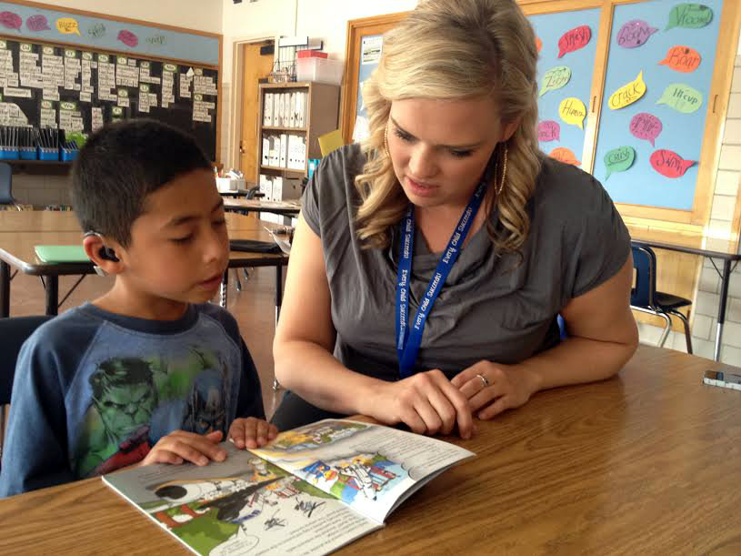 <p>Third grade teacher Kyle Schwartz of Doull Elementary helps Chris Flores with some extra reading practice. Schwartz posted some of her students #IWishMyTeacherKnew responses to Twitter and they went viral. </p>