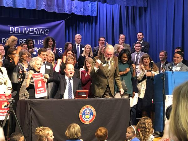 Gov. Jared Polis celebrates with lawmakers at Stedman Elementary School after signing the bill to fund full-day kindergarten.