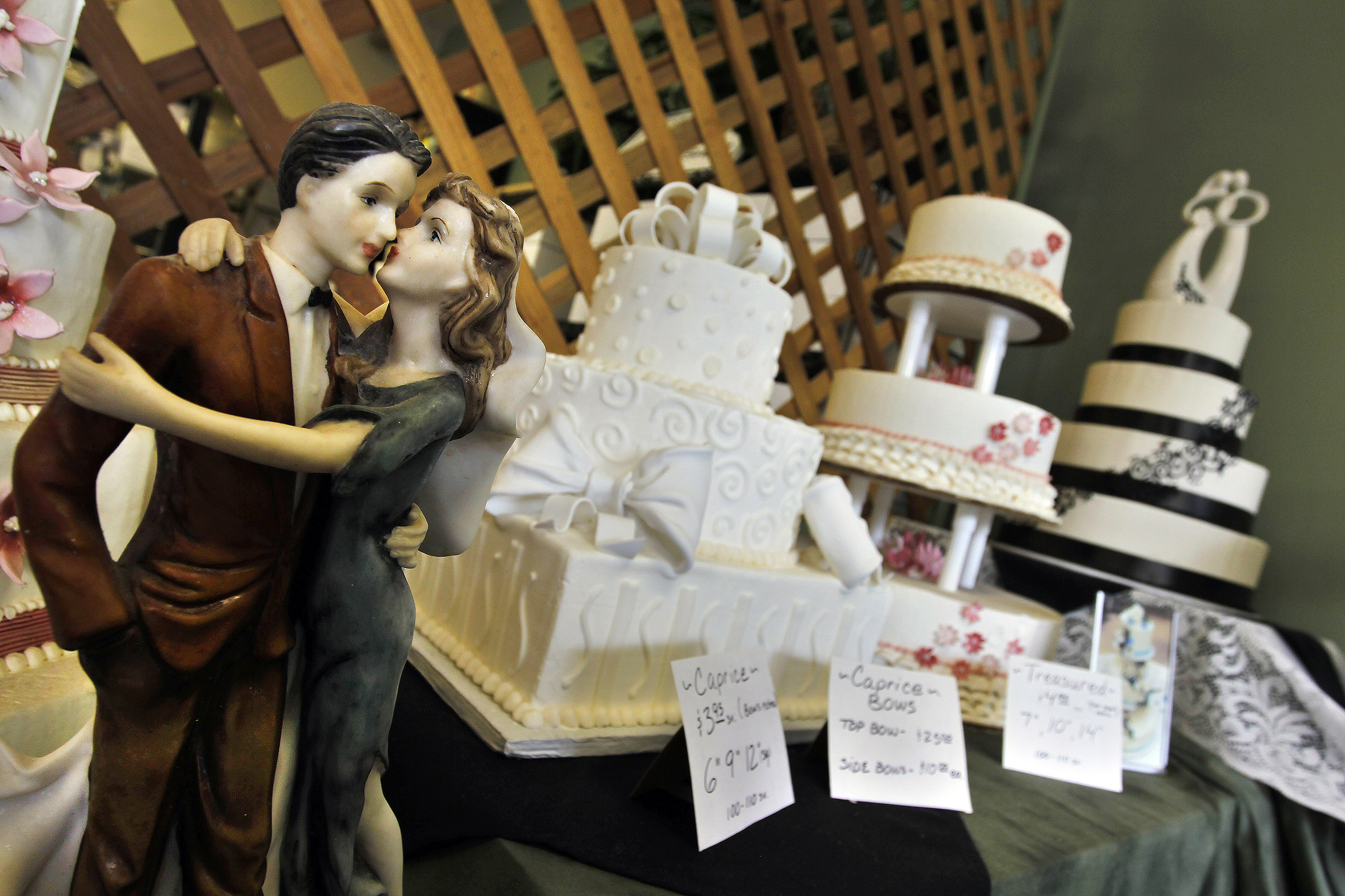 <p>Figurines are depicted in an embrace as part of the wedding cake display at Masterpiece Cakeshopin Denver, Thursday, June 6, 2013.</p>