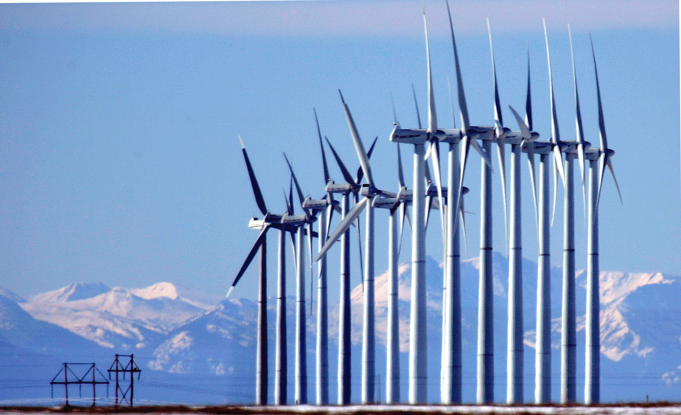 <p>The Rocky Mountains can be seen in the distance as wind mills generate electricity at the Ponnequin Wind Farm near Carr, Colo.</p>