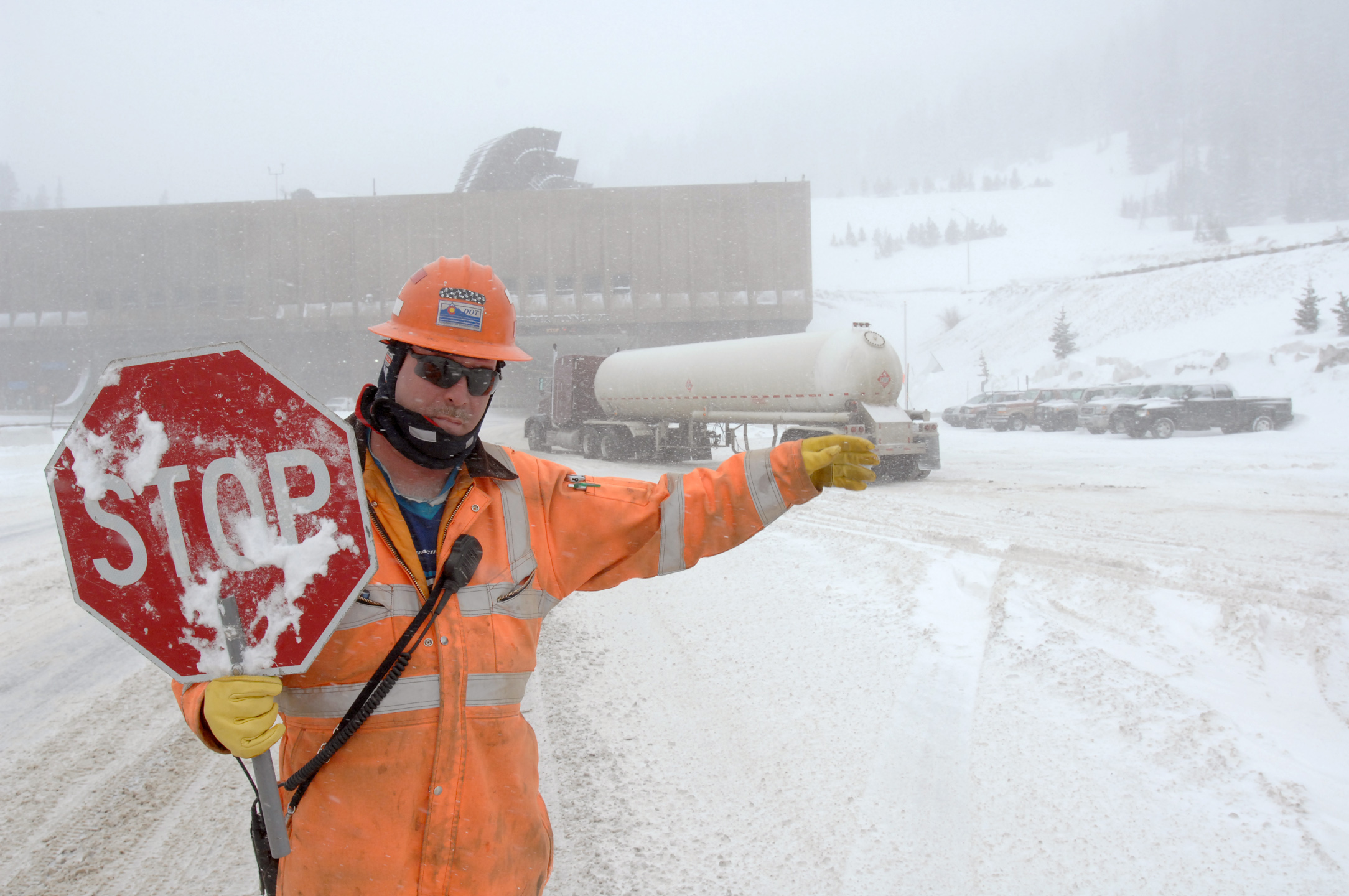 <p>Colorado Department Transportation worker George Fischer halts westbound Interstate 70 traffic at the east portal to the 11,300 foot Eisenhower Tunnel in a 2008 snowstorm to allow vehicles carrying hazardous materials through. High winds and blowing snows created dangerous conditions which closed Loveland Pass where hazmat vehicles usually travel.</p>