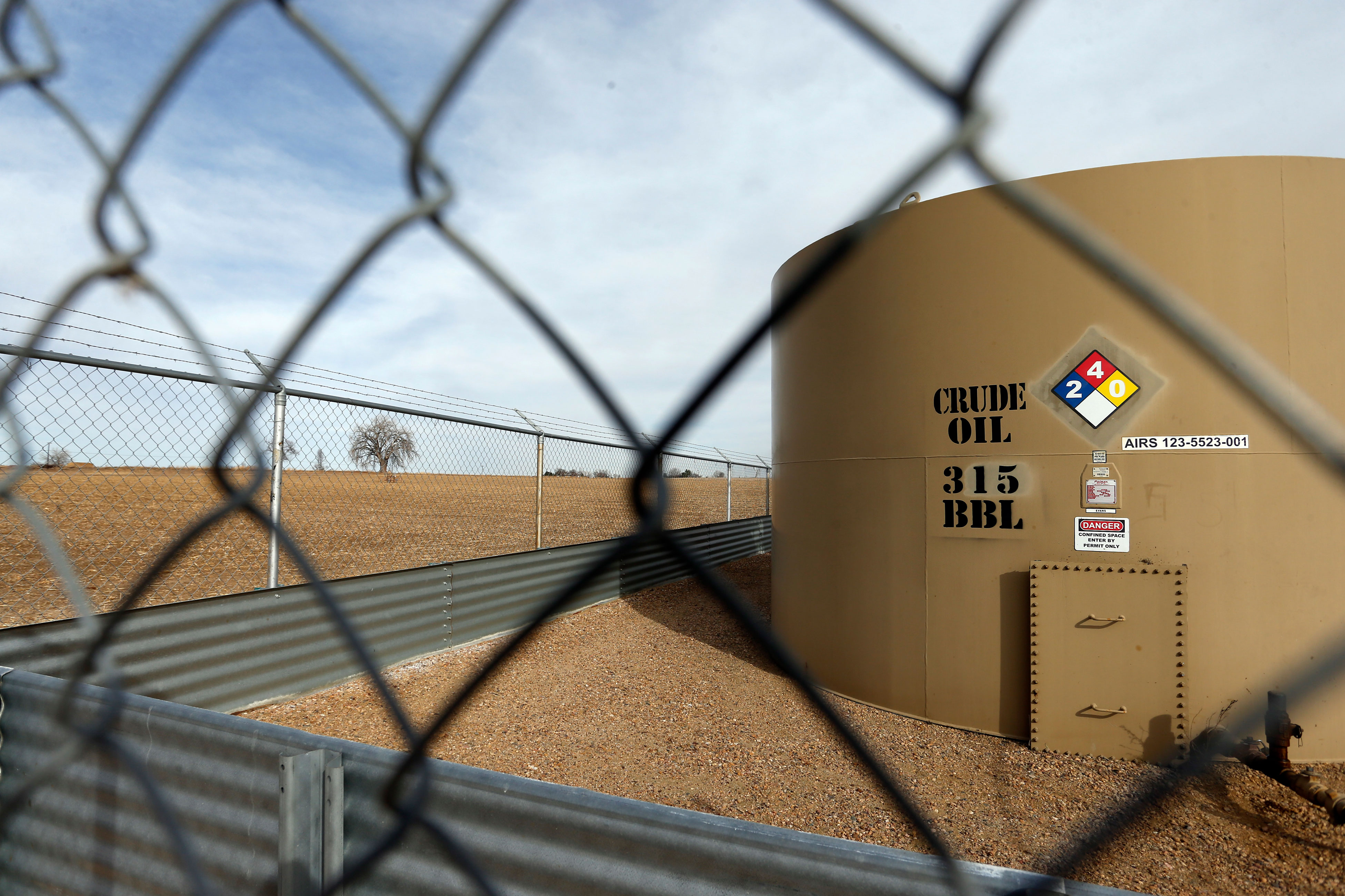A crude oil storage tank sits behind a fence at a petroleum extraction site, in Weld County, near Mead, Colo., Monday, Feb. 13, 2017.