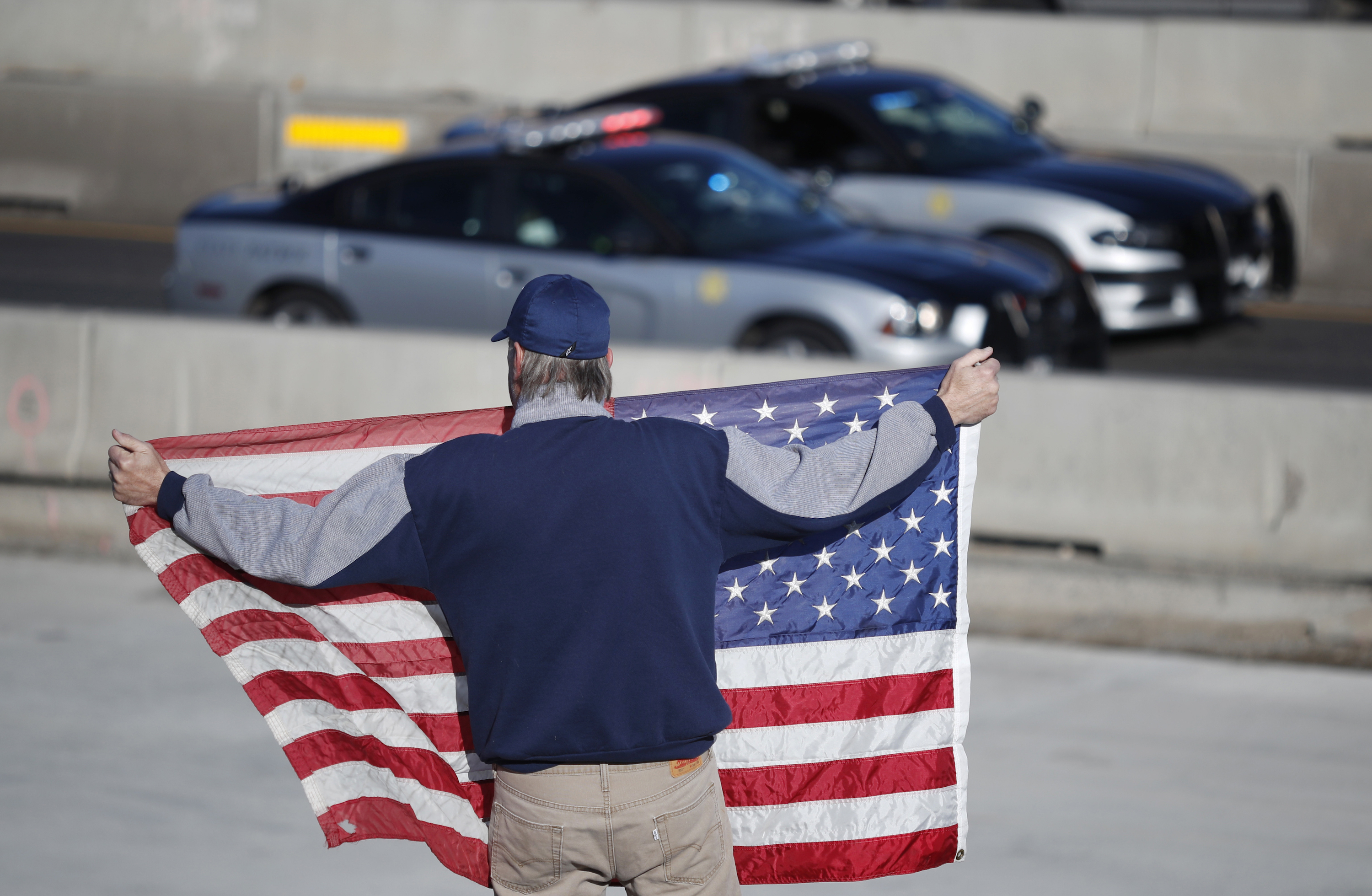 <p>David Morgan of Highlands Ranch, Colo., holds an American flag as a procession of law enforcement vehicles accompanies a hearse carrying the body of a sheriff's deputy shot and killedSunday, Dec. 31, 2017, in Highlands Ranch, Colo.</p>