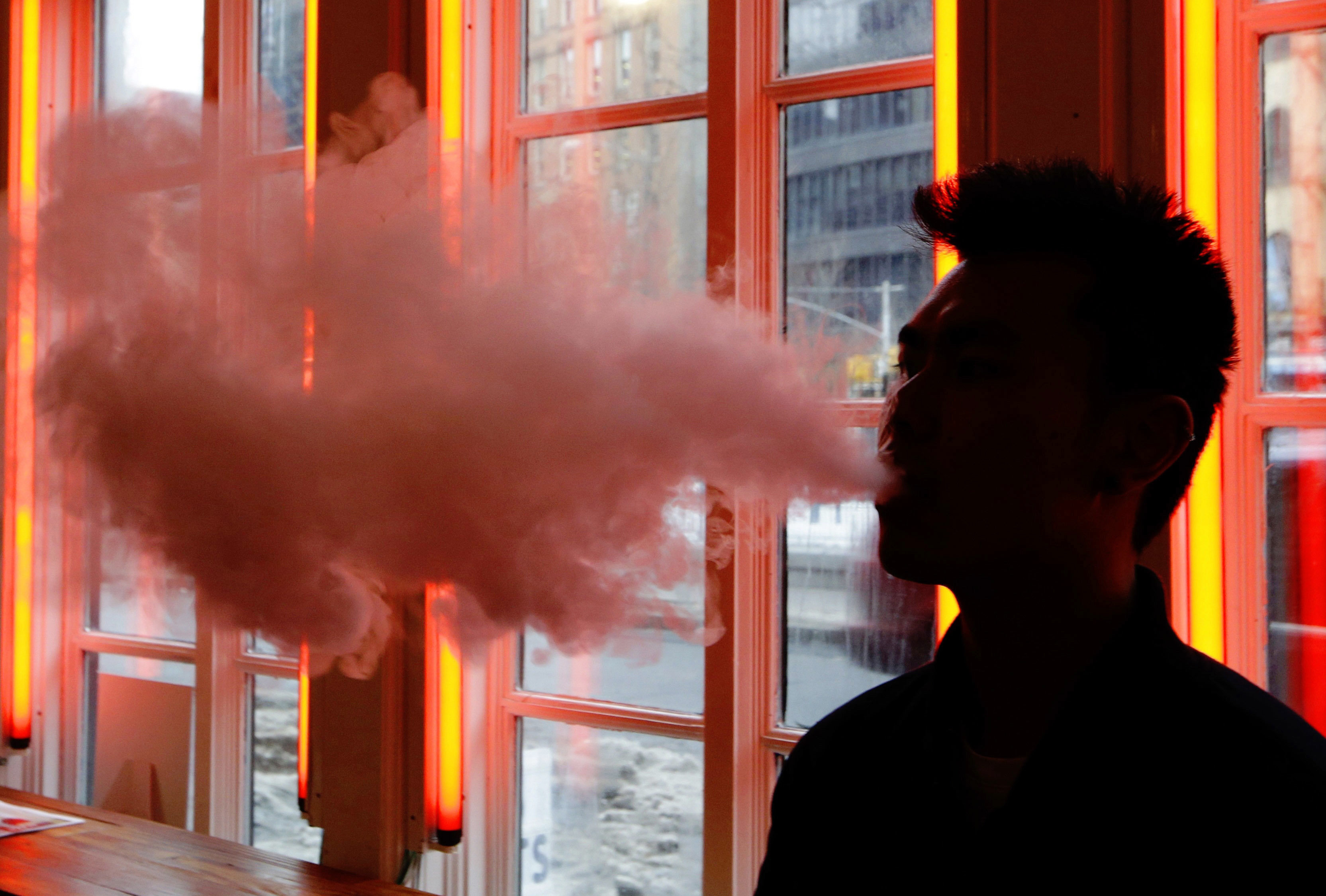 A customer exhales vapor from an e-cigarette at a store in New York onFeb. 20, 2014.