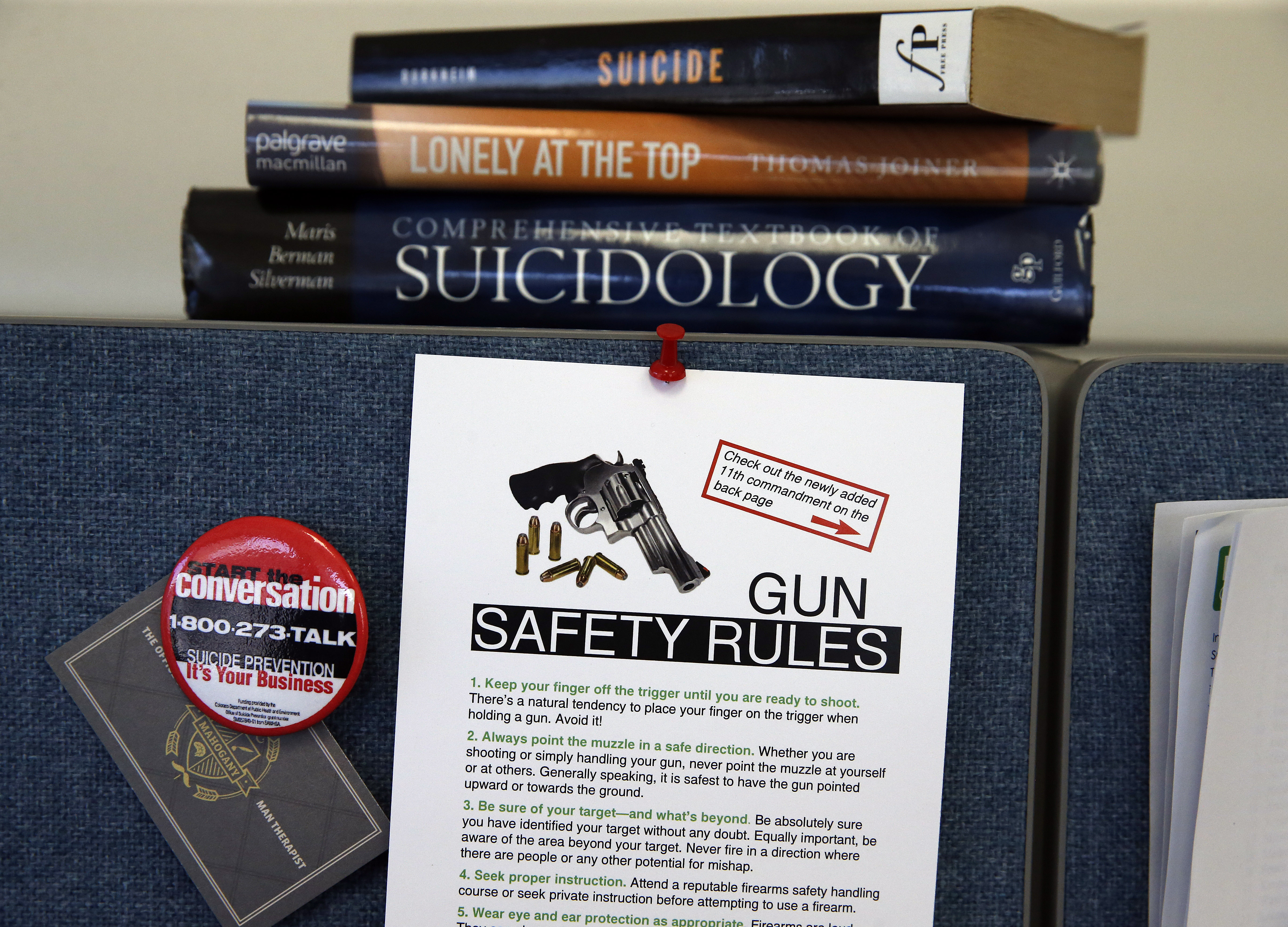 In this March 11, 2016 photo, gun safety and suicide prevention literature on the shelf inside the office of Jarrod Hindman, director of Colorado's Office of Suicide Prevention, in Denver.