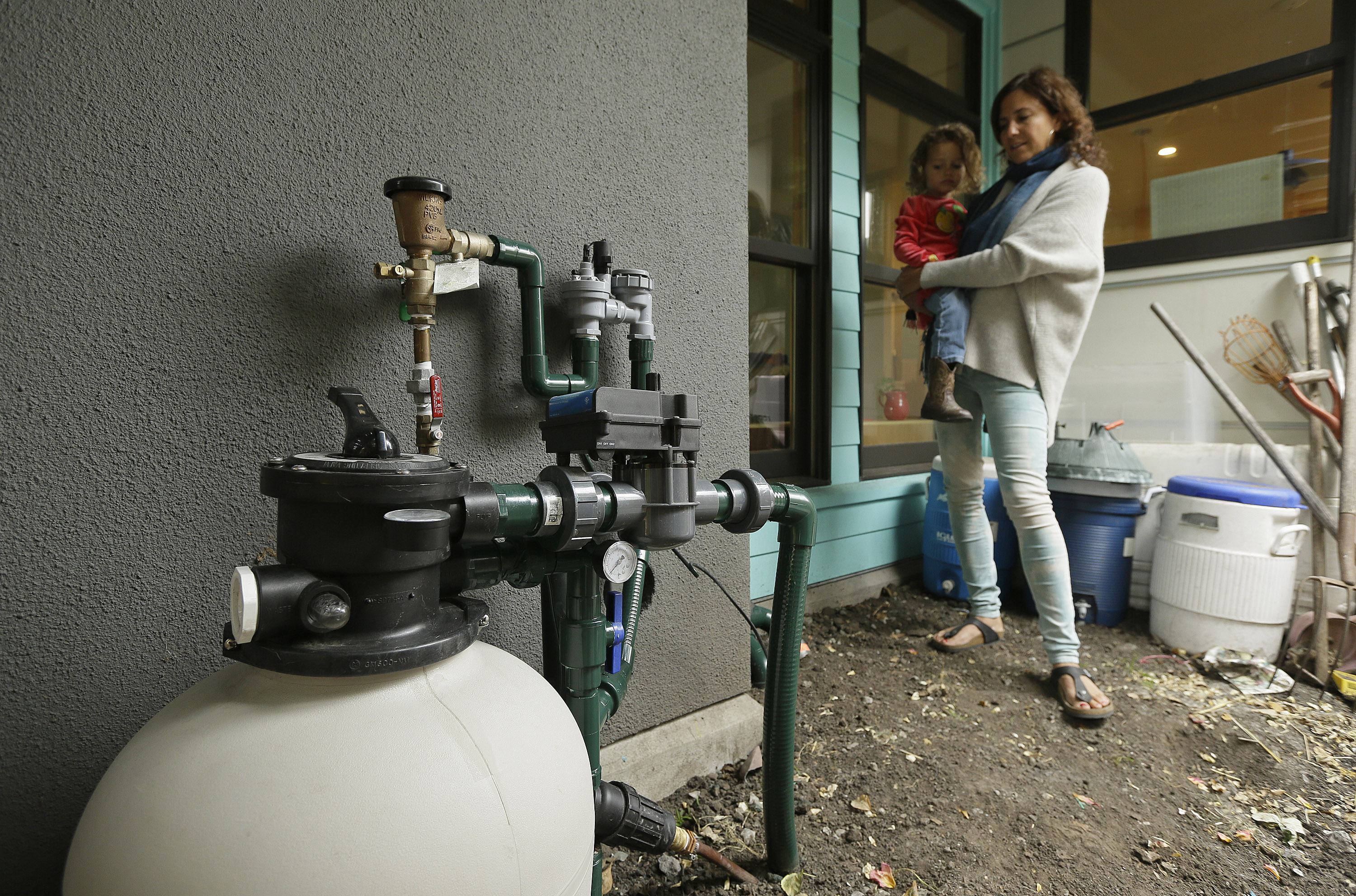 <p>In thisMay2015 photo, Catarina Negrin holds preschooler Alana Nichols while standing near a graywater filtering system outside her home in Berkeley, Calif. Graywater is recycled waste water from kitchen appliances, bath tubs, showers and sinks.</p>