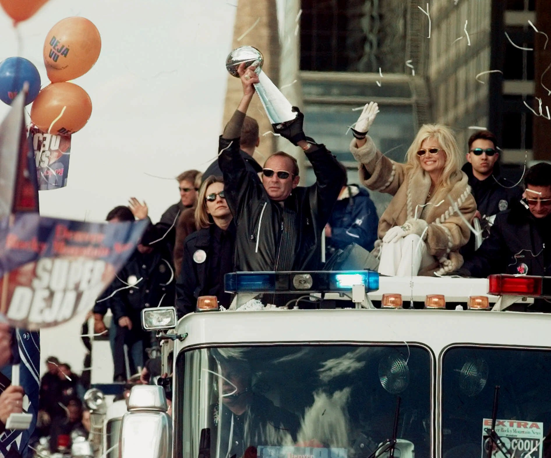 <p>Denver Broncos owner Pat Bowlen holds the Vince Lombardi Super Bowl trophy over his head and his wife, Annabelle, right, waves, as they ride a fire truck through downtown Denver in a victory parade on Monday, Feb. 1, 1999.</p>