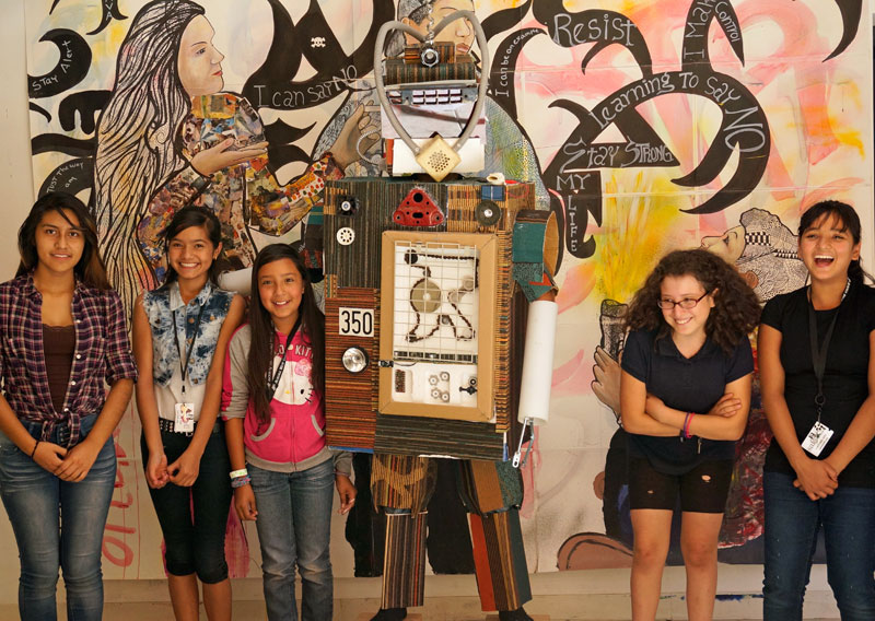 """<p>DAVA youth pose with an """"ArtBot,"""" a robotmade entirely out of recycled materials.</p>"""
