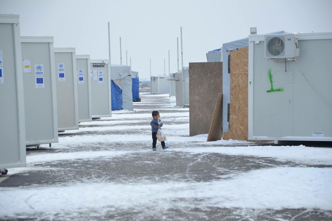 <p>A 5-year old boy in the Nea Kavalarefugee camp in Greece walks to his shipping container with a bag of food that volunteers distributed. Thetemperature was in the single digits and the boy had nohat or gloves.</p>