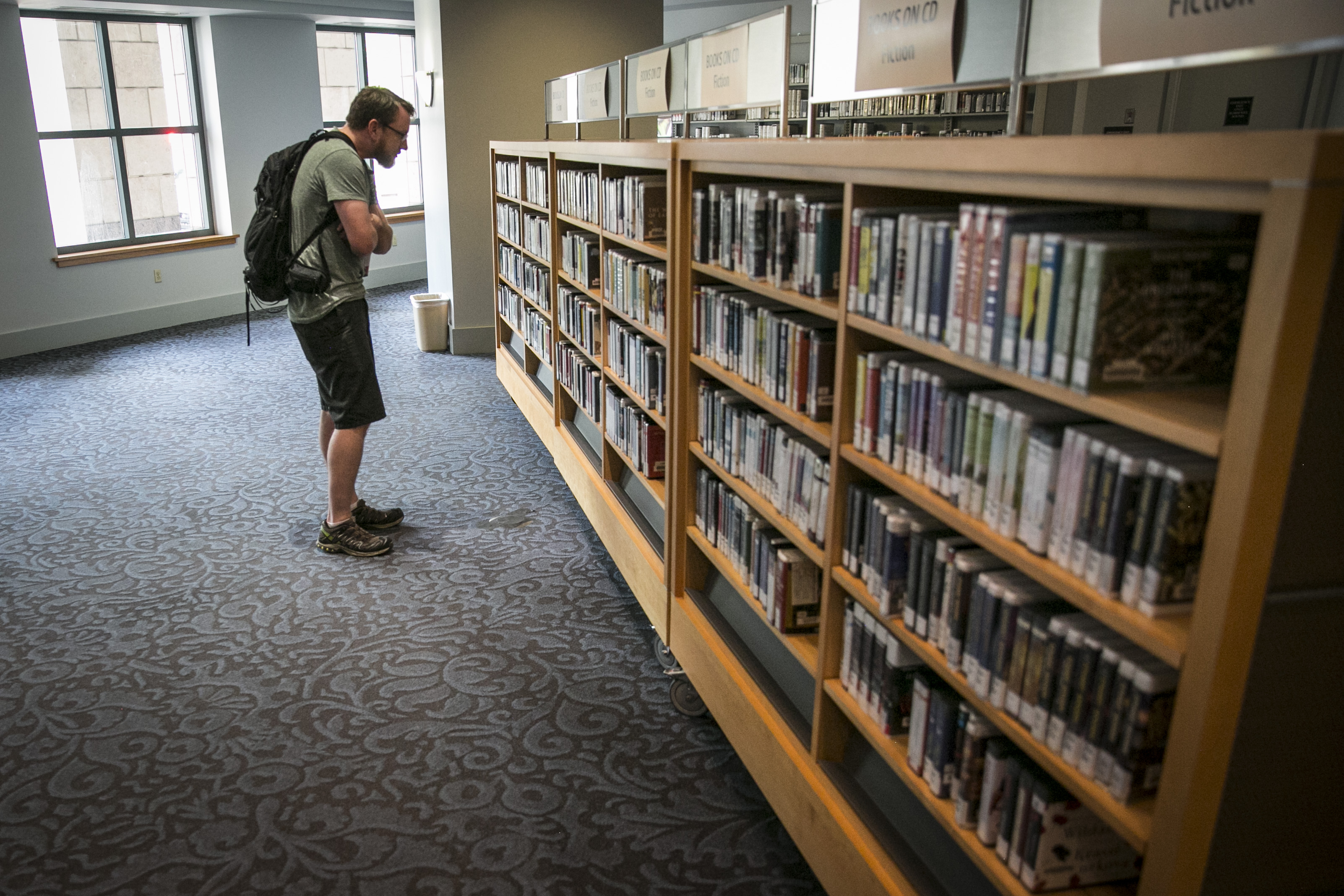 Brett Normandin of Denver peruses the audio book section of the Denver Central Library on Thursday, May 25, 2017.