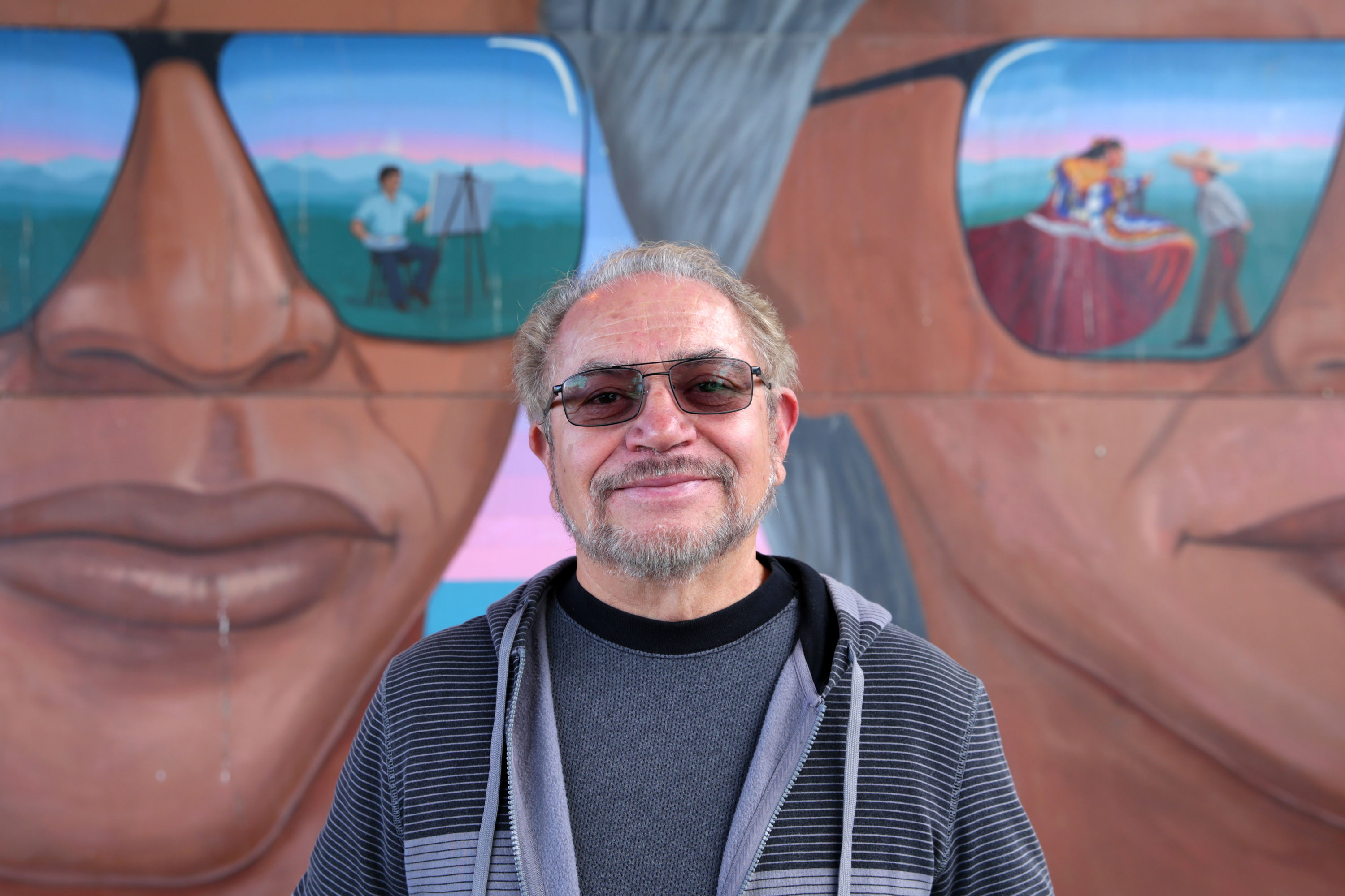 "<p>Emanuel Martinez stands in front of his Denver mural ""Confluent People"" on Friday, Oct. 21, 2016.</p>"