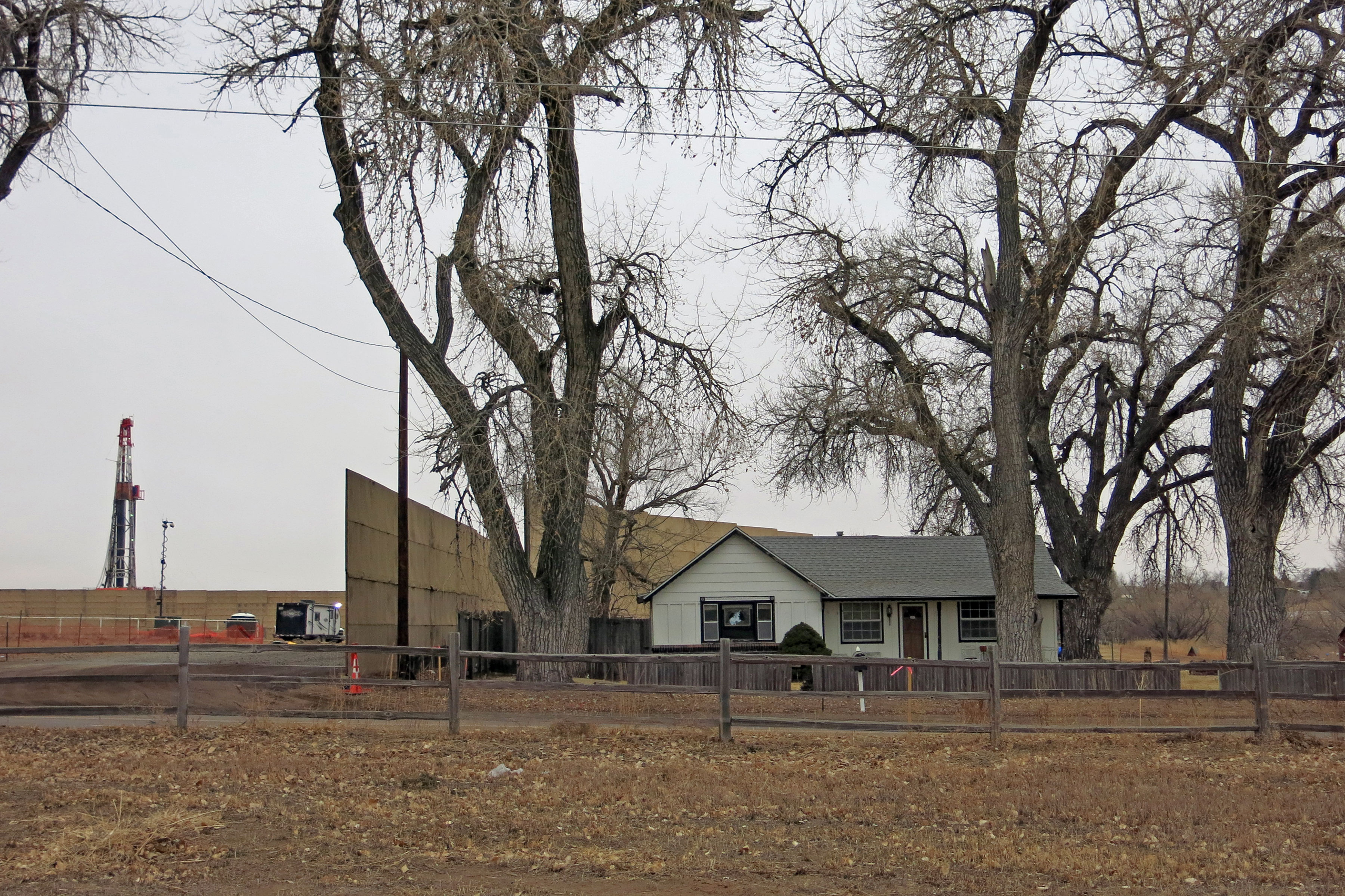 <p>Dawn Stein's home near the Triple Creek drilling site in Greeley, Colo. The access road for the site is directly to the left of her home and the sound wall installed to mitigate impacts.</p>