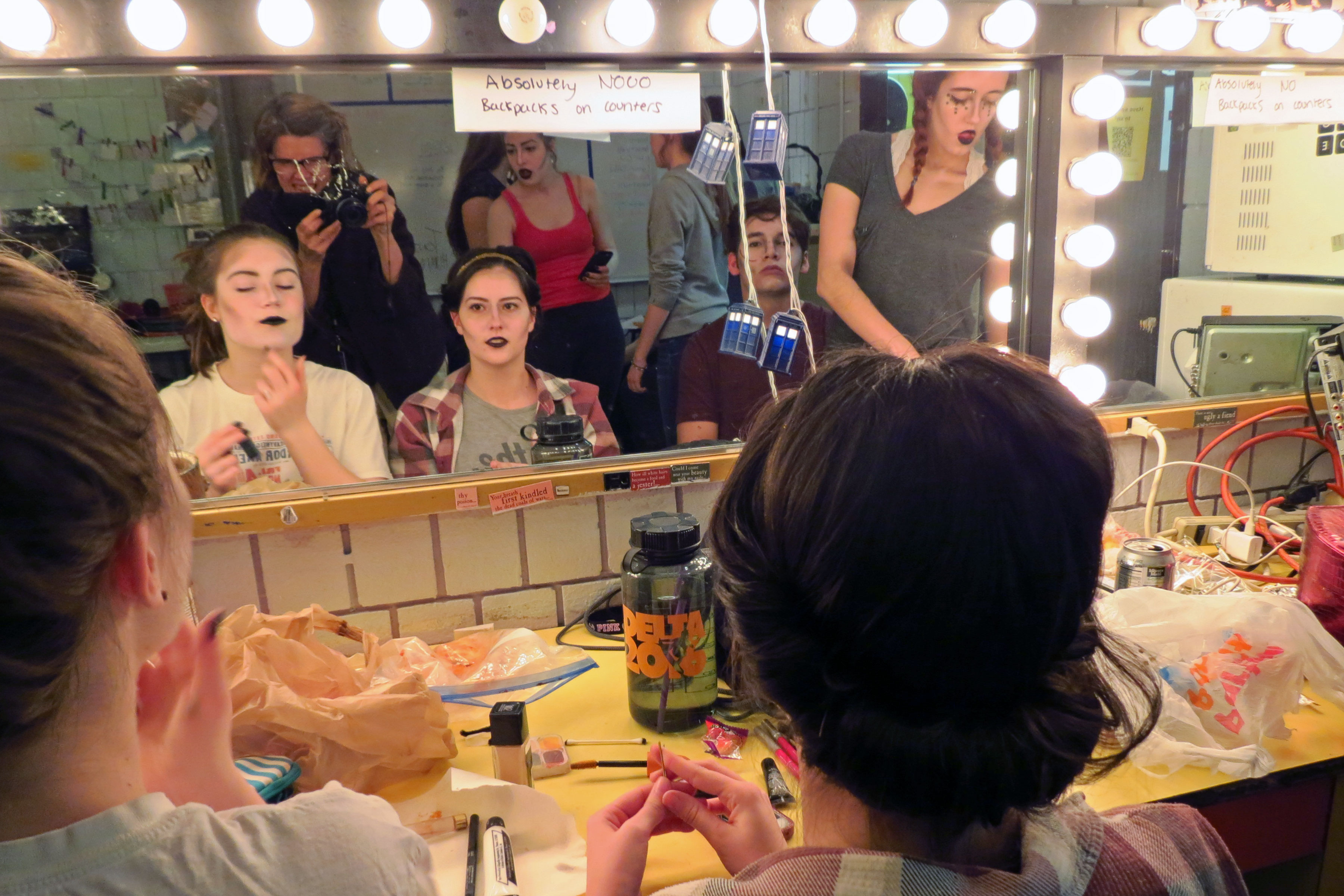 "<p>Brianna Martinez watches Eden Farr apply costume make up before showtime at the school's production of ""The Addams Family.""</p>"