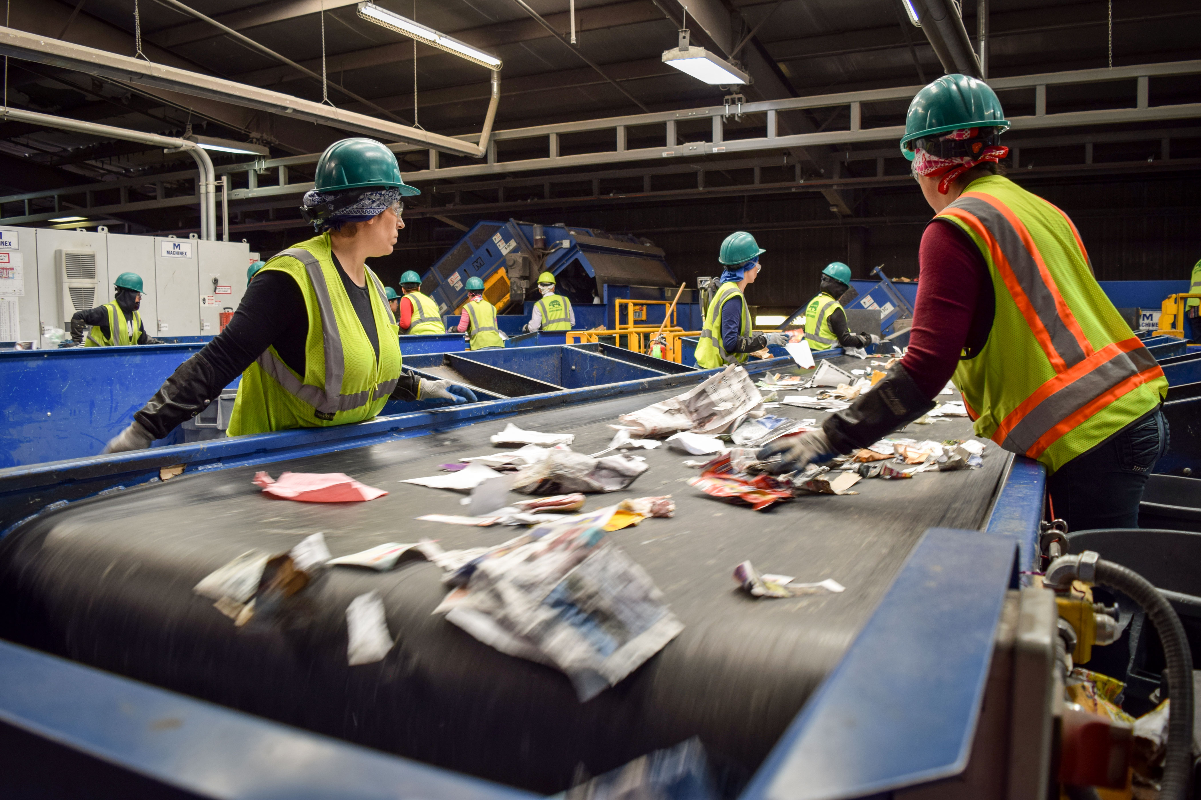 Workers look for items that can not be recycled at Alpine Waste and Recycling in Denver on June 19, 2018.