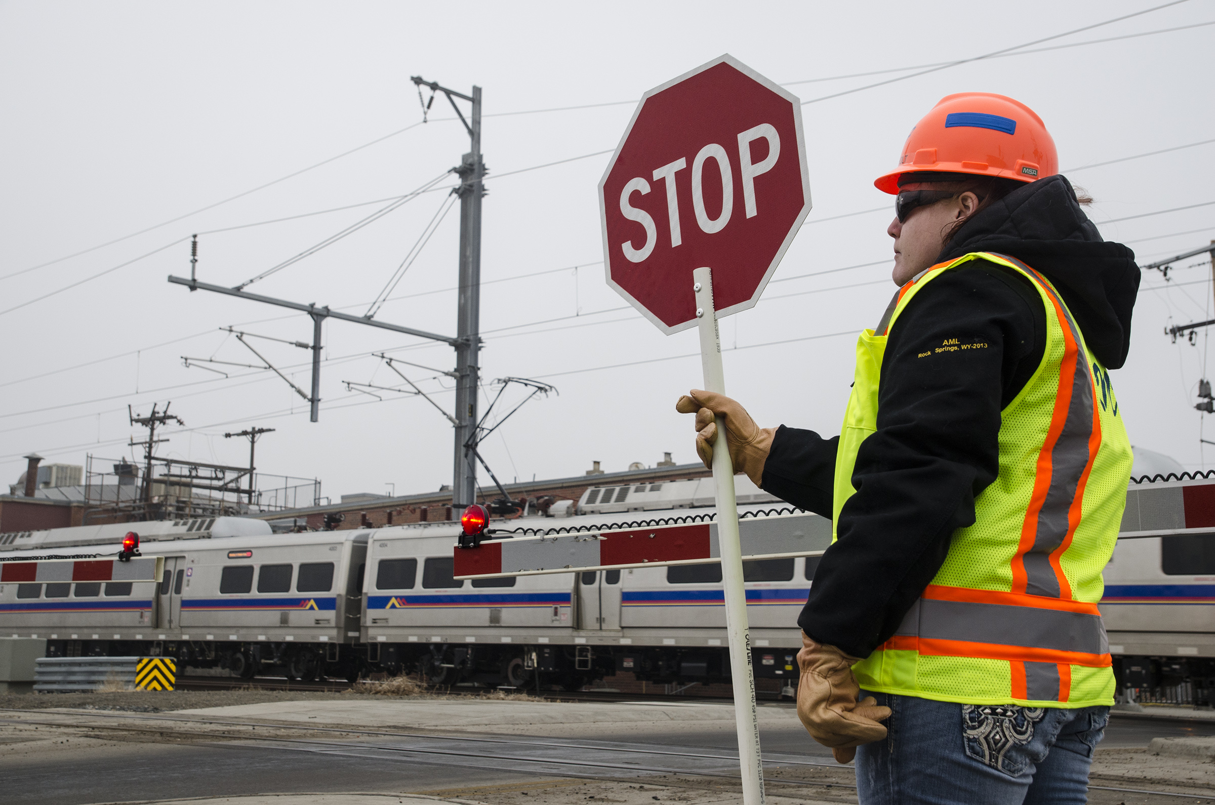 <p>A contractor posted at the A Line crossing at Steele Street in north Denver holds a stop sign on Tuesday, Jan. 24, 2017. The flaggers are required at each grade crossing along the A and B lines until issues with the lines' positive train control system are resolved.</p>
