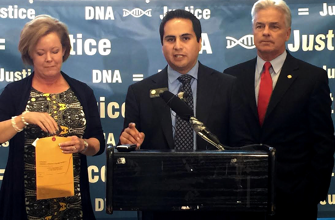 <p>GOP state Rep. Polly Lawrence, left, places a swab of Democratic state Rep. DanPabon's DNA into an envelope, asDenver District Attorney Mitch Morrissey, at right, looks on.Similar DNA tests would be done for several new misdemeanor criminals if their co-sponsored bill is passed into law.</p>