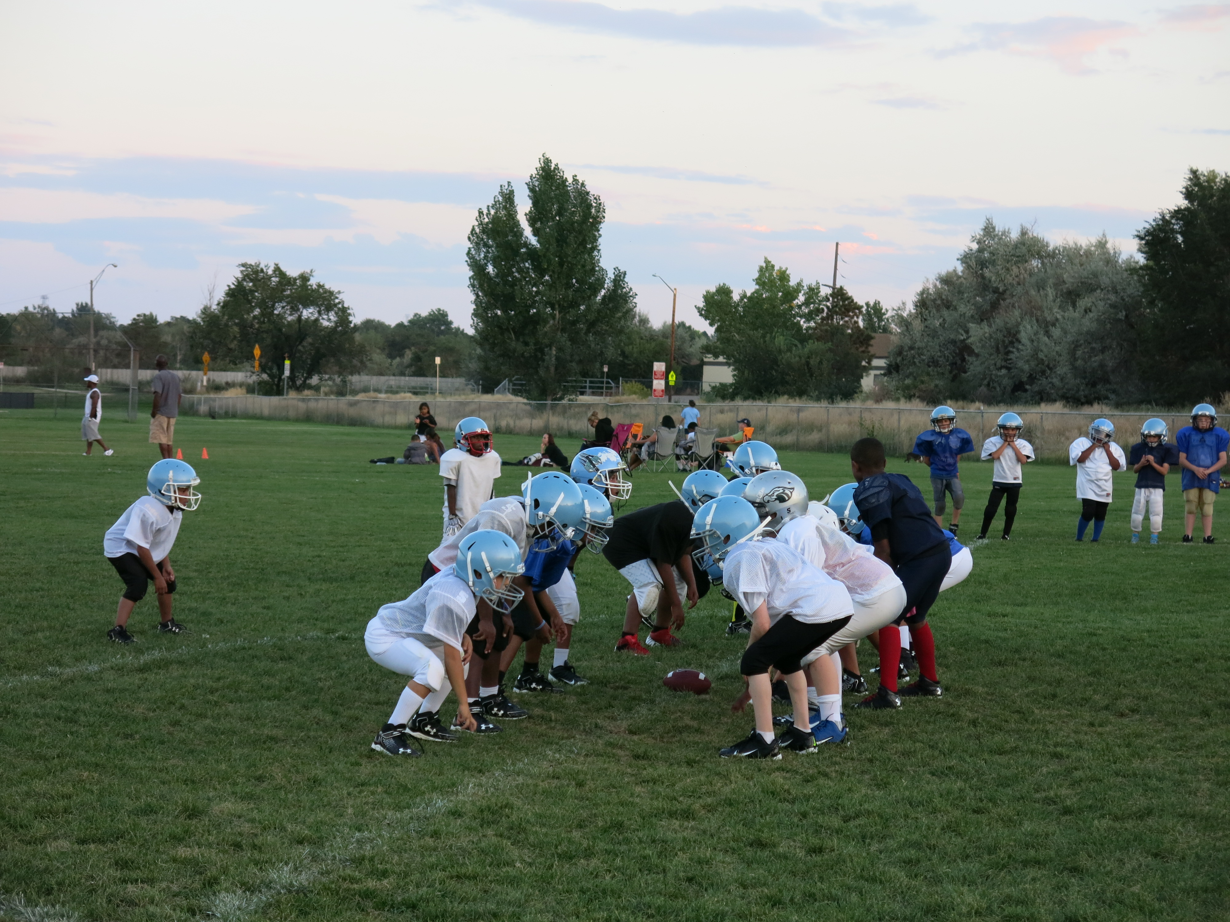 <p>A group of 9-year-old football players with Cougar Youth Sports practices on a recent evening in Aurora.</p>