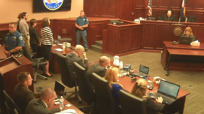 <p>The scene in the courtroom at sentencing as James Holmes, standing at far left with hands in pockets, learns his fate after being found guilty of killing 12 people and injuring 70 in the 2012 Aurora theater shooting.</p>