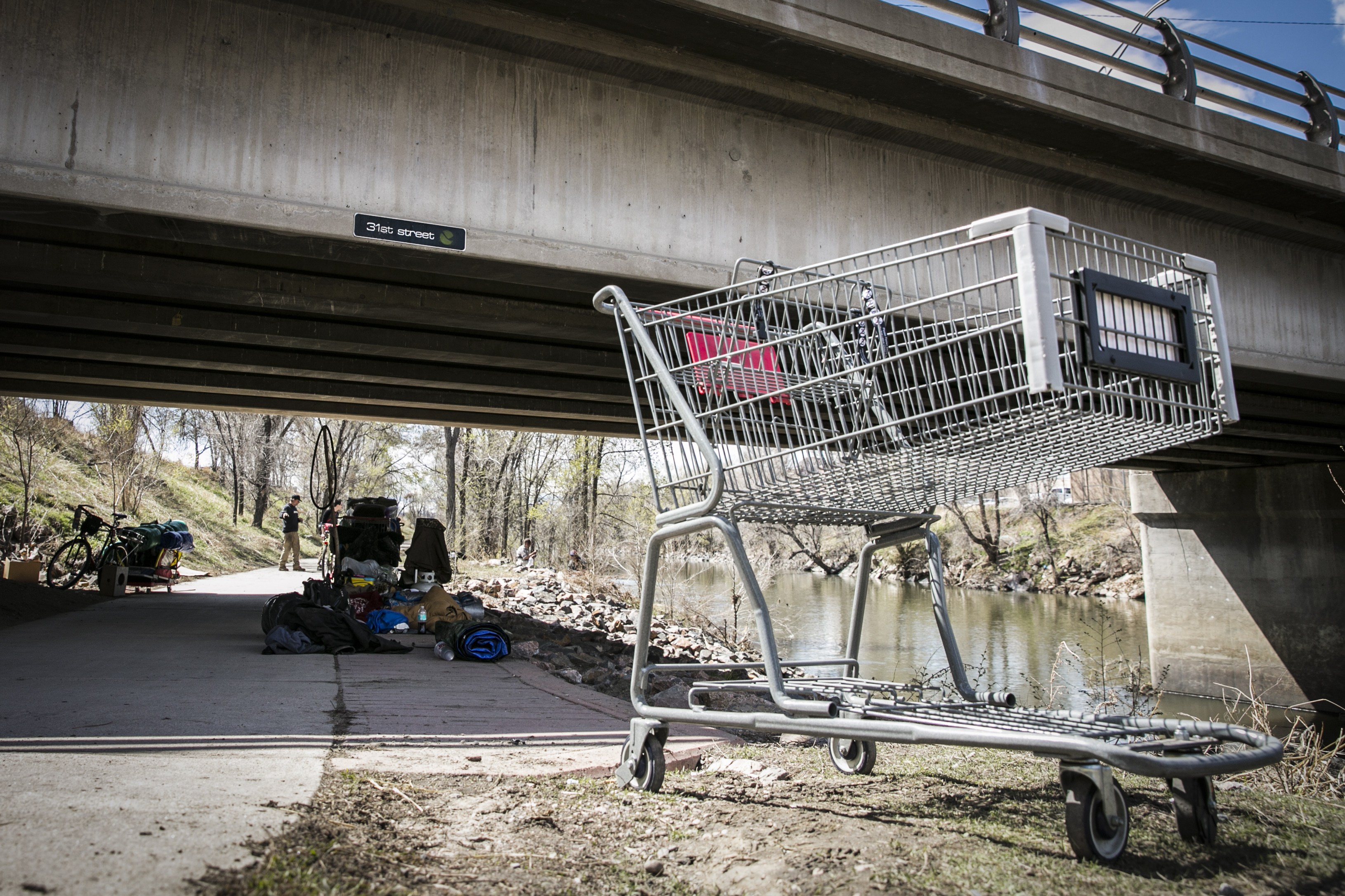 A shopping cart rests near a temporary homeless camp by the 31st Street Bridge near the South Platte River outside of downtown Denver on Friday, April 1, 2016.