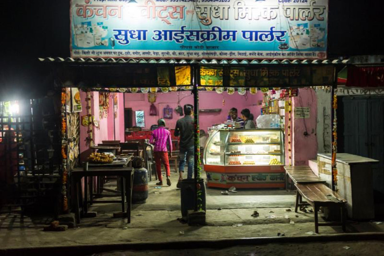 <p>Electric light allows a Husk Power Systems customer in the Indian state of Bihar to to keep his shop open until 11 p.m., which increases business.</p>