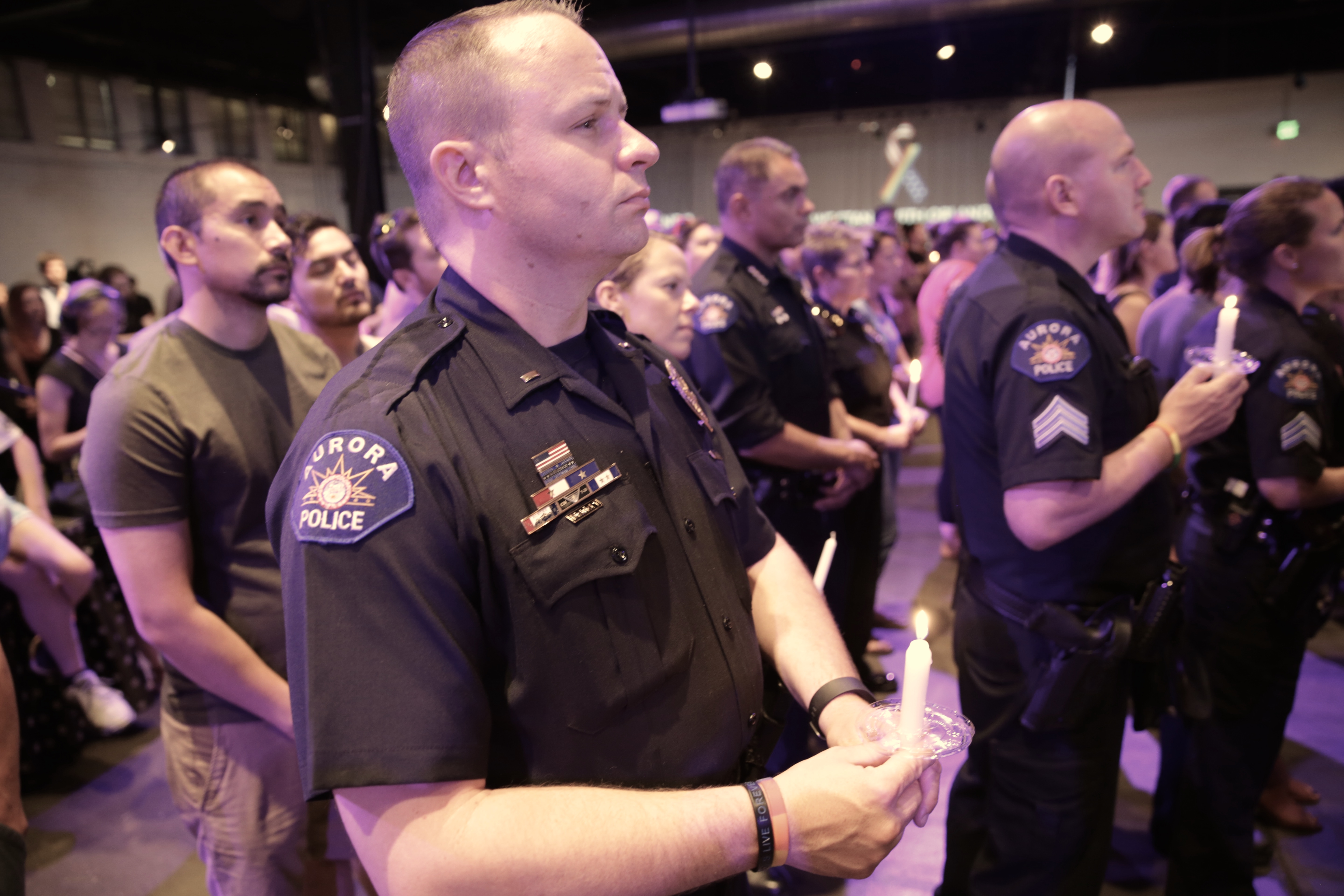 <p>Aurora Police Department officers hold candles Sunday evening at Tracks nightclub in Denver during avigil for victims of the mass shooting in Orlando.</p>