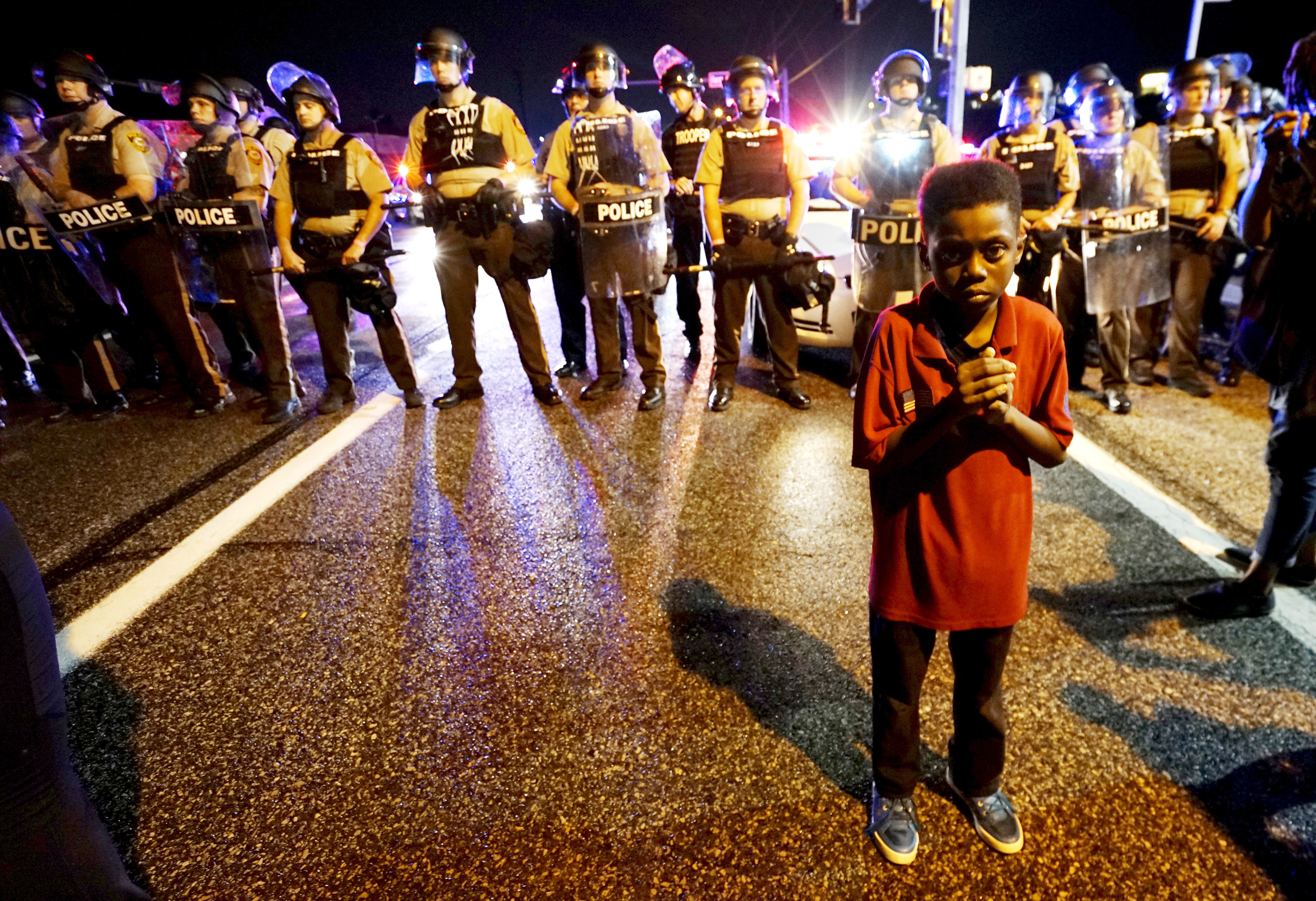 <p>Amarion Allen, 11-years-old, stands shivering in fear in the 90 degree heat with his mother protesting nearby in front of a police line shortly before shots were fired in a police-officer involved shooting in Ferguson, Missouri August 9, 2015. </p>