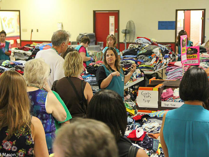 <p>Tour participants view the fellowship hall of the relief center inside Sacred Heart Catholic Church in McAllen, Texas, where new immigrants can get meals and donated clothing. </p>