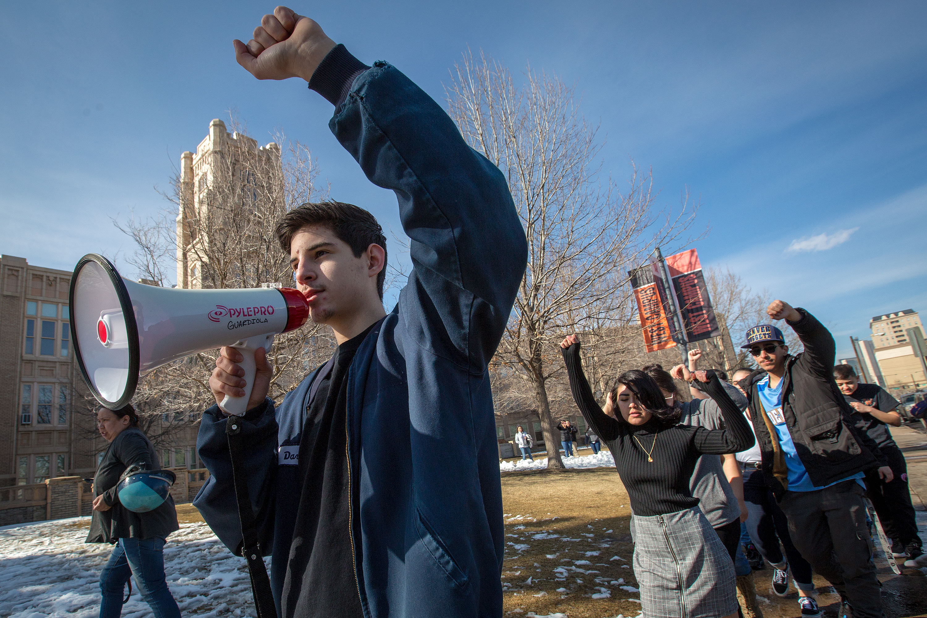 <p>West High School student Esai Lopez, carrying a bullhorn, takes part in a re-enactment of the West High School Blowout on Feb. 26, 2019.</p>