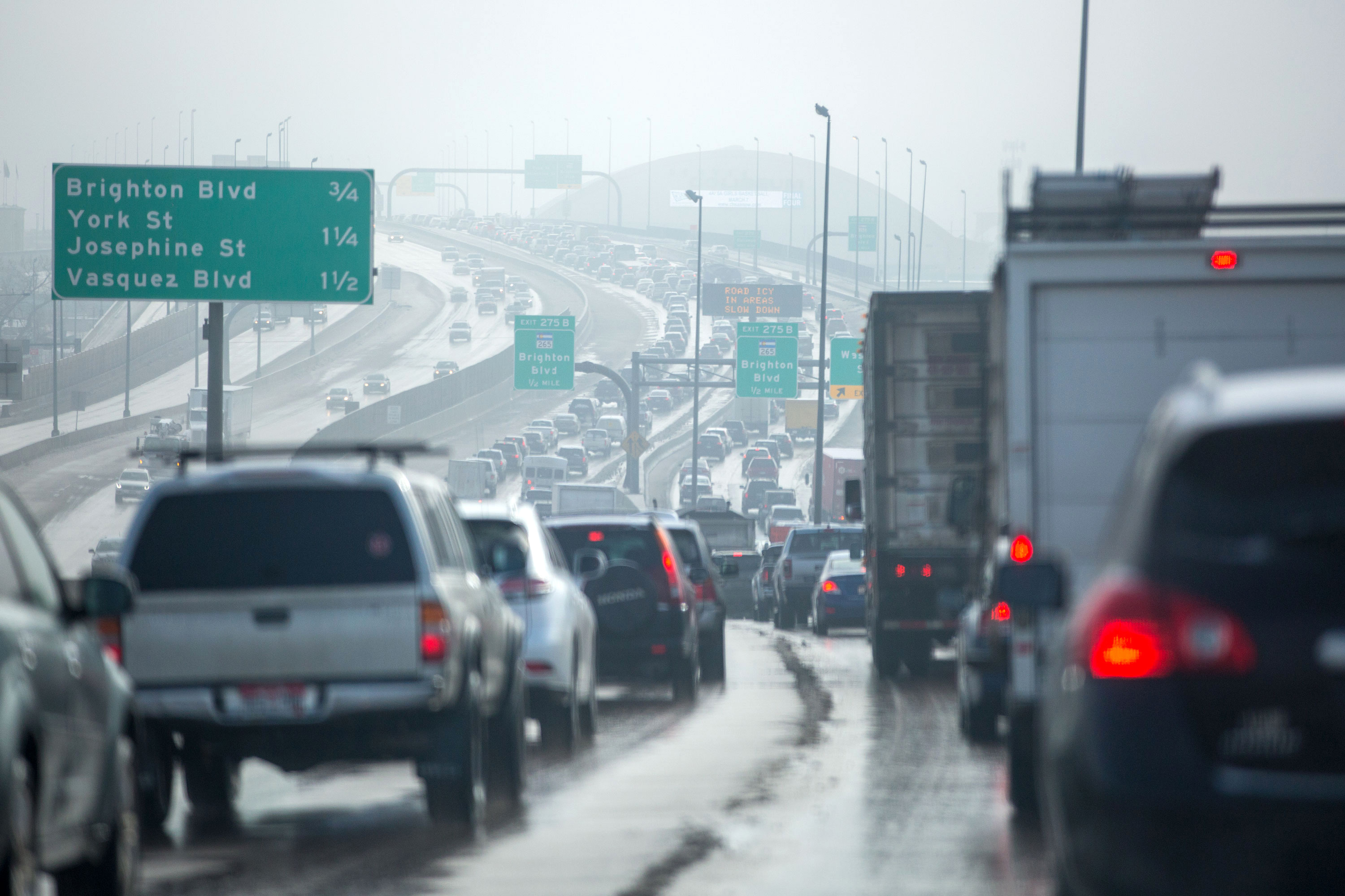 Air pollution envelopes the morning commute on Interstate 70 near the National Western Center in Denver Thursday March 7 2019.