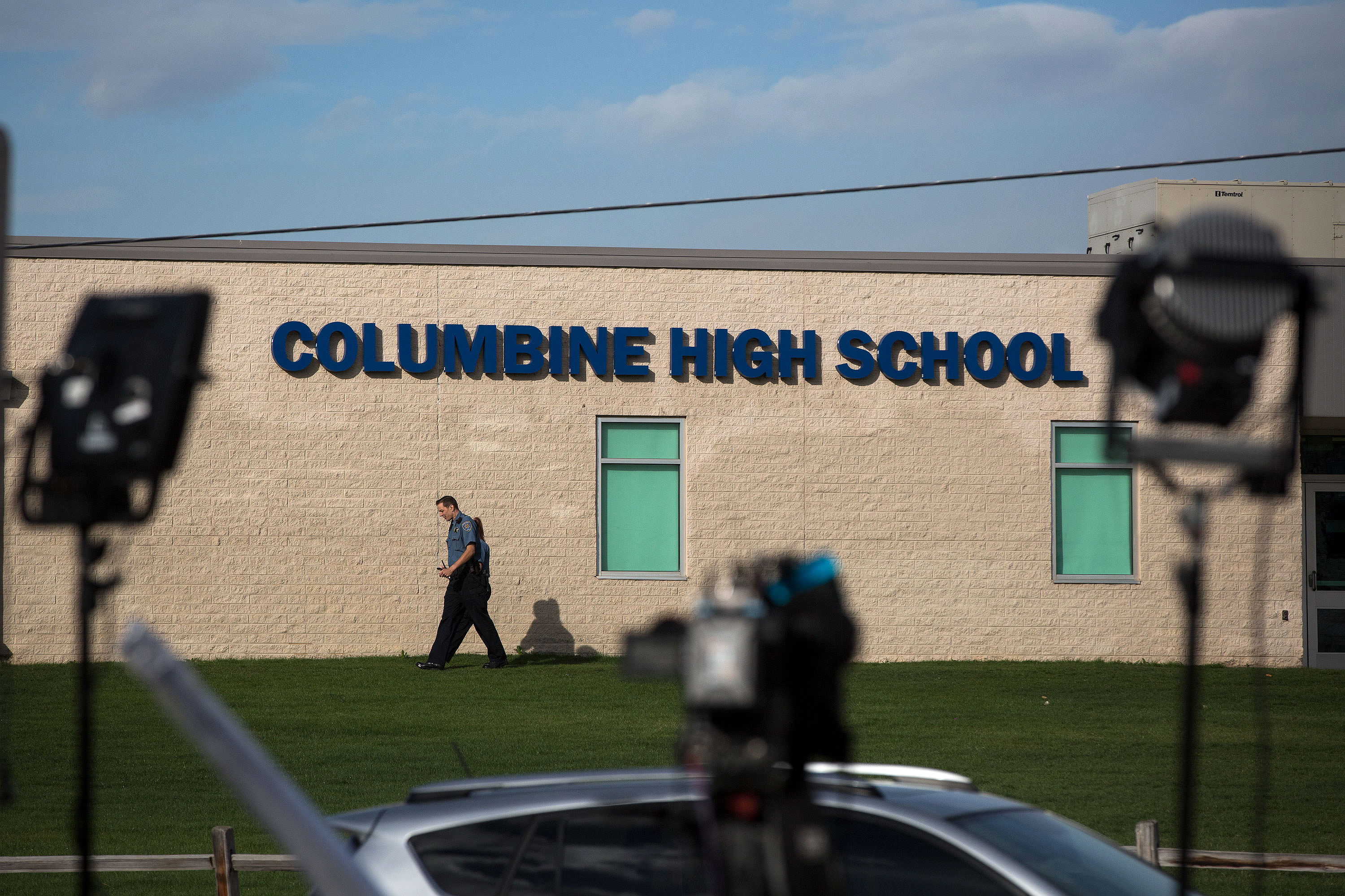 <p>Law enforcement officers walk outside Columbine High School under the gaze of televisions cameras on Wednesday April 17 2019.</p>