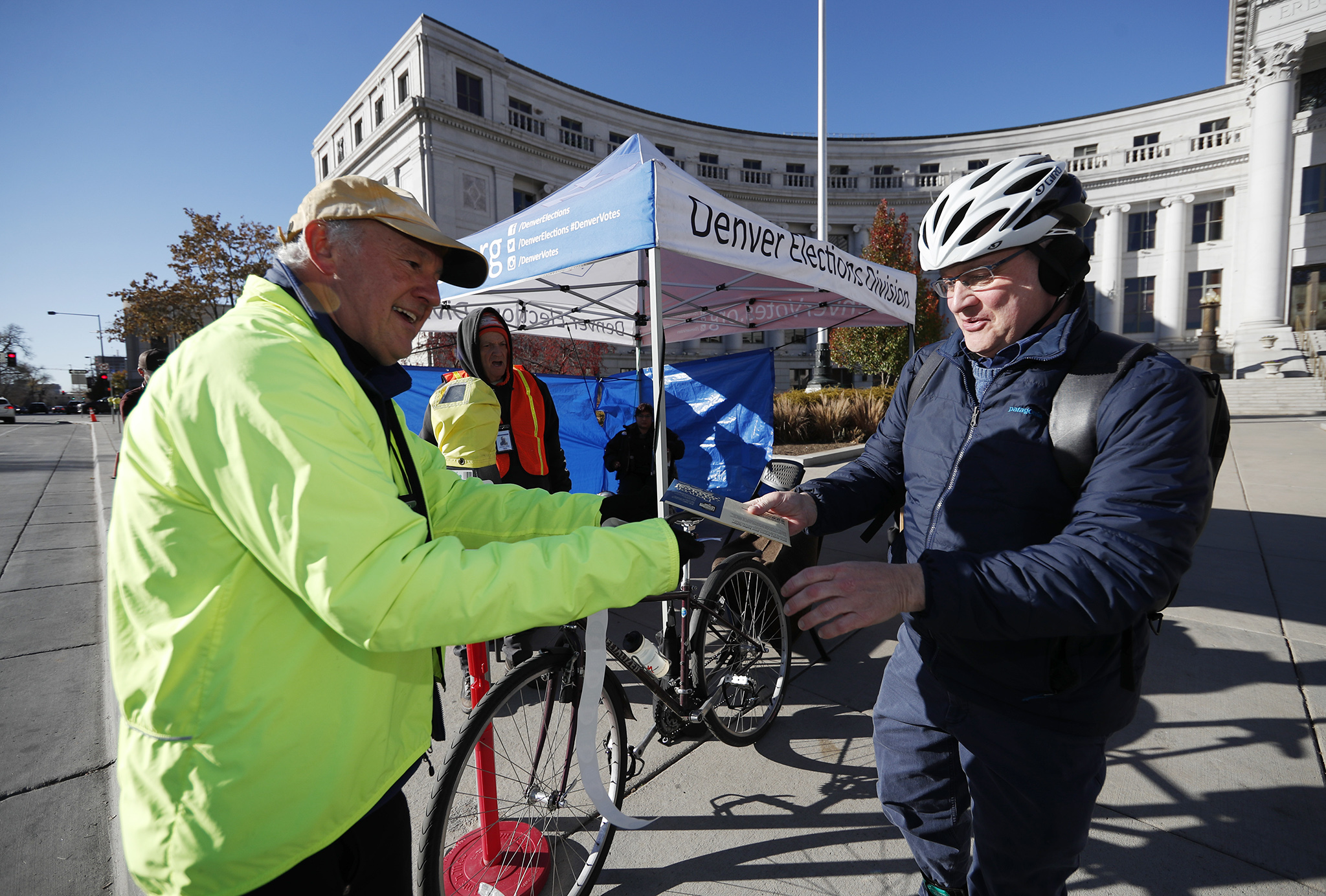 Election judge Michael Michalek, left, takes ballots from voter Lee Cryer as he drops them off at the Denver Elections Division location in front of the City/County Building Tuesday, Nov. 6, 2018, in Denver.