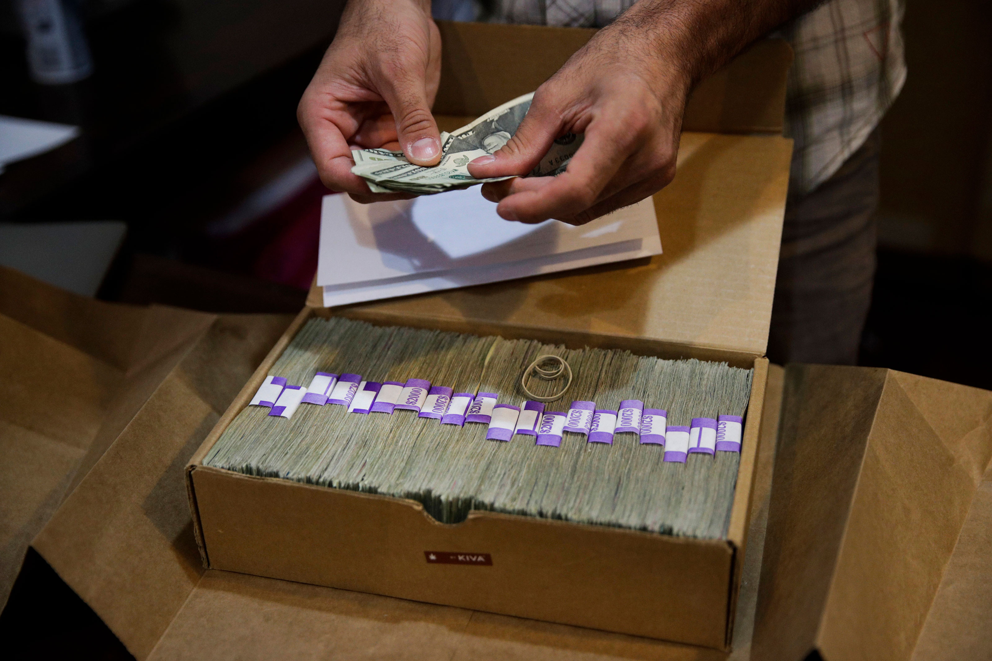 The proprietor of a medical marijuana dispensary prepares his monthly tax payment, over $40,000 in cash, at his Los Angeles store, June 27, 2017.
