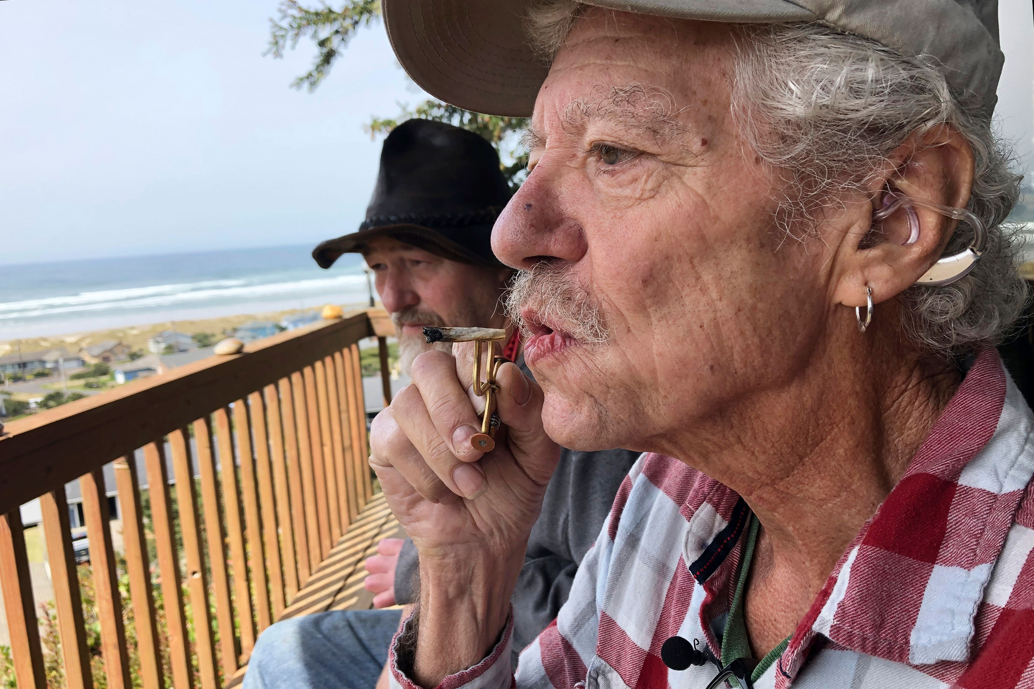 <p>Two-time cancer survivor and medical marijuana cardholder Bill Blazina, 73, smokes a marijuana joint on the deck of his neighbor's home in Waldport, Ore., April 25, 2019.</p>