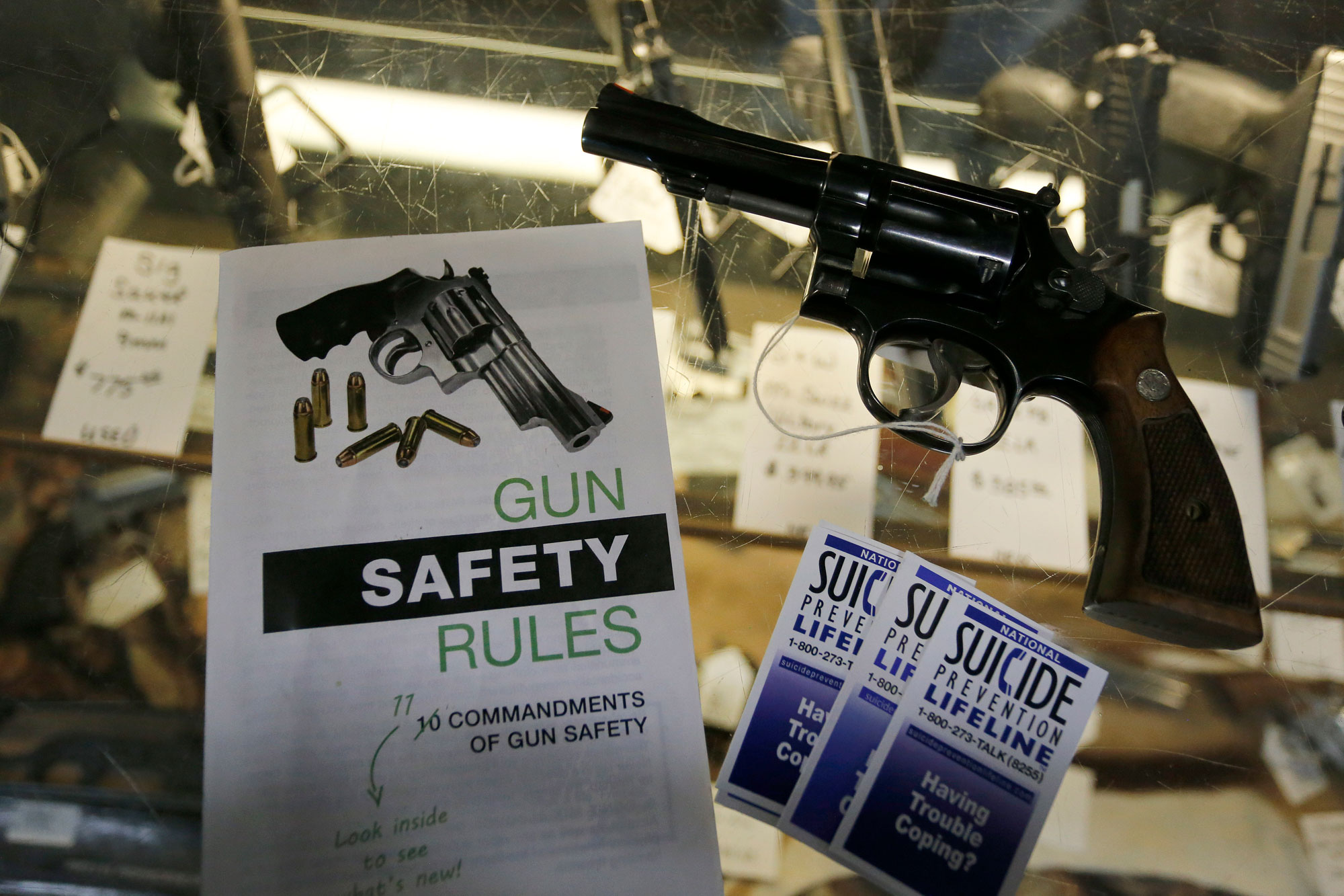 In this Feb. 23, 2016 photo, gun safety and suicide prevention brochures on display next to guns for sale at a local retail gun store in Montrose, Colo.