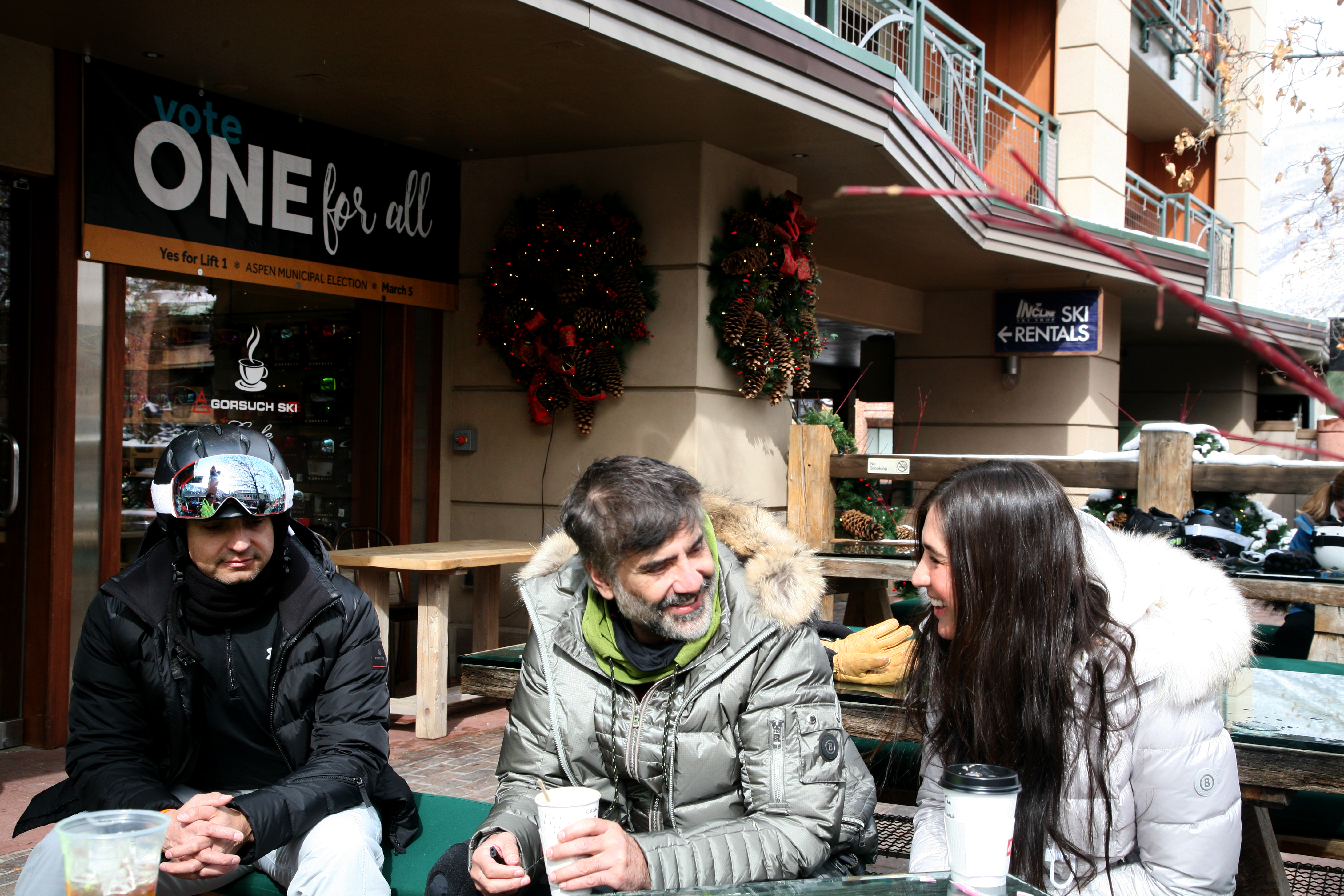 <p>Signs in support of Lift One are visible all across Aspen, though the project is controversial. From left, Mexican visitors Rafael Orozco, Alejandro Fernandez and Karla Laveaga drink coffee at the base of the mountain.</p>