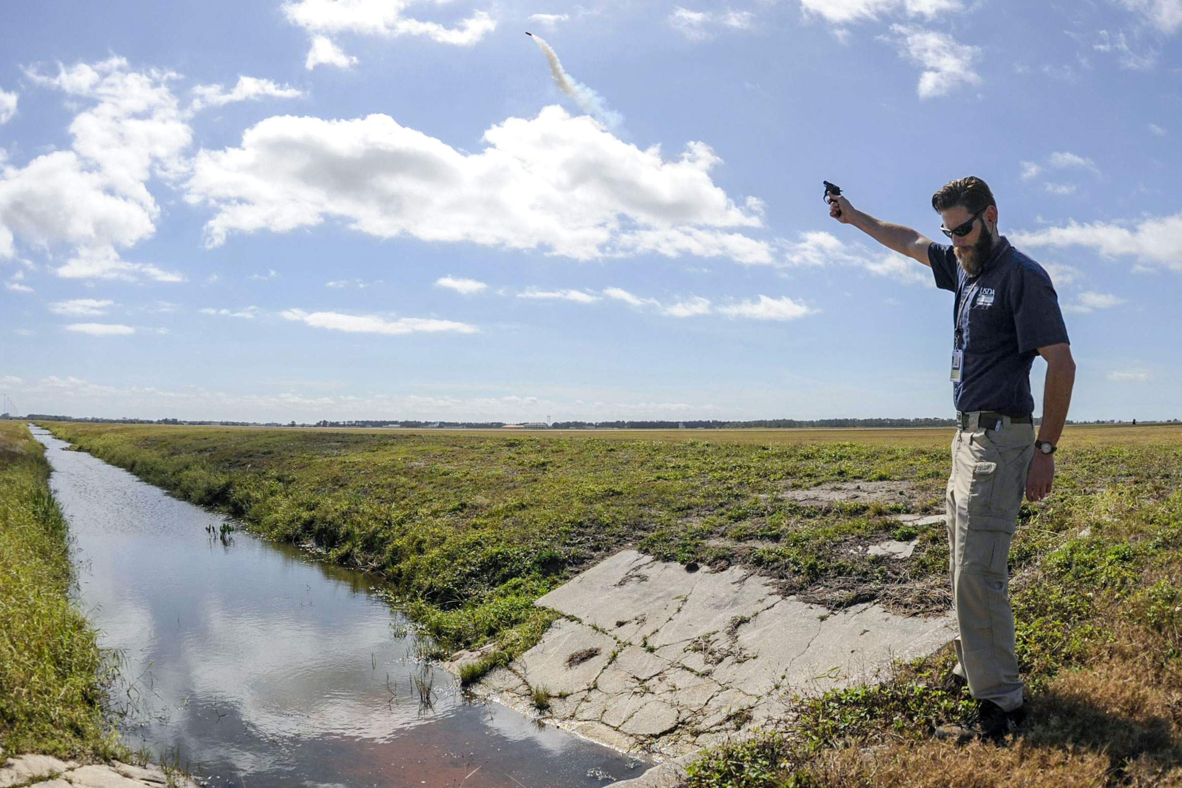 <p>Wildlife biologist Kory McLellan shoots off pyrotechnics to scare birds away from the airfield at MacDill Air Force Base in Tampa, Fla.</p>