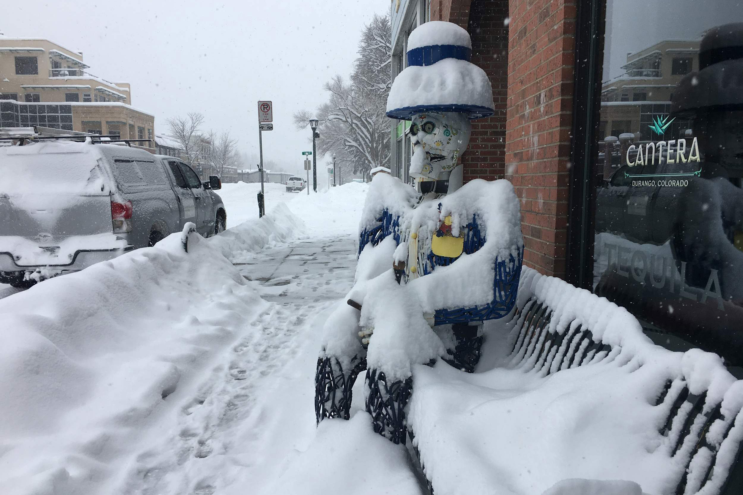<p>A skeleton man takes in the big snowfall has theysiton bench in front of CanteraRestaurtant in Durango, Colo., Feb. 21, 2019.</p>