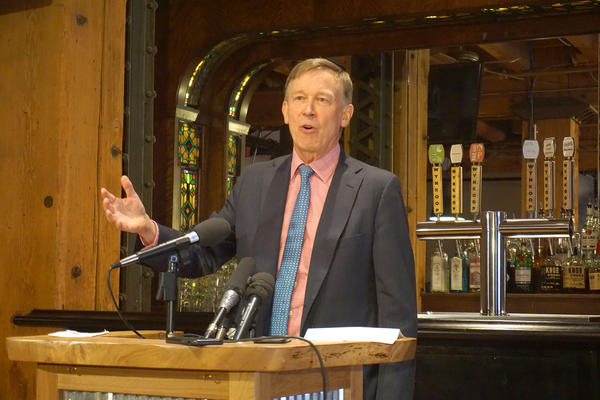 Former Colorado Gov. John Hickenlooper speaks to reporters about the launch of his presidential campaign in downtown Denver.