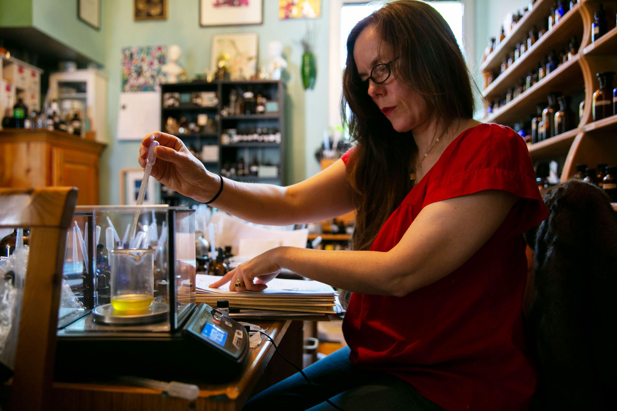 Perfumer Dawn Spencer Hurwitz uses a pipette to prepare a delicate mix of scents in a new perfume she is developing at her Boulder work space on Tuesday, June 4, 2019.