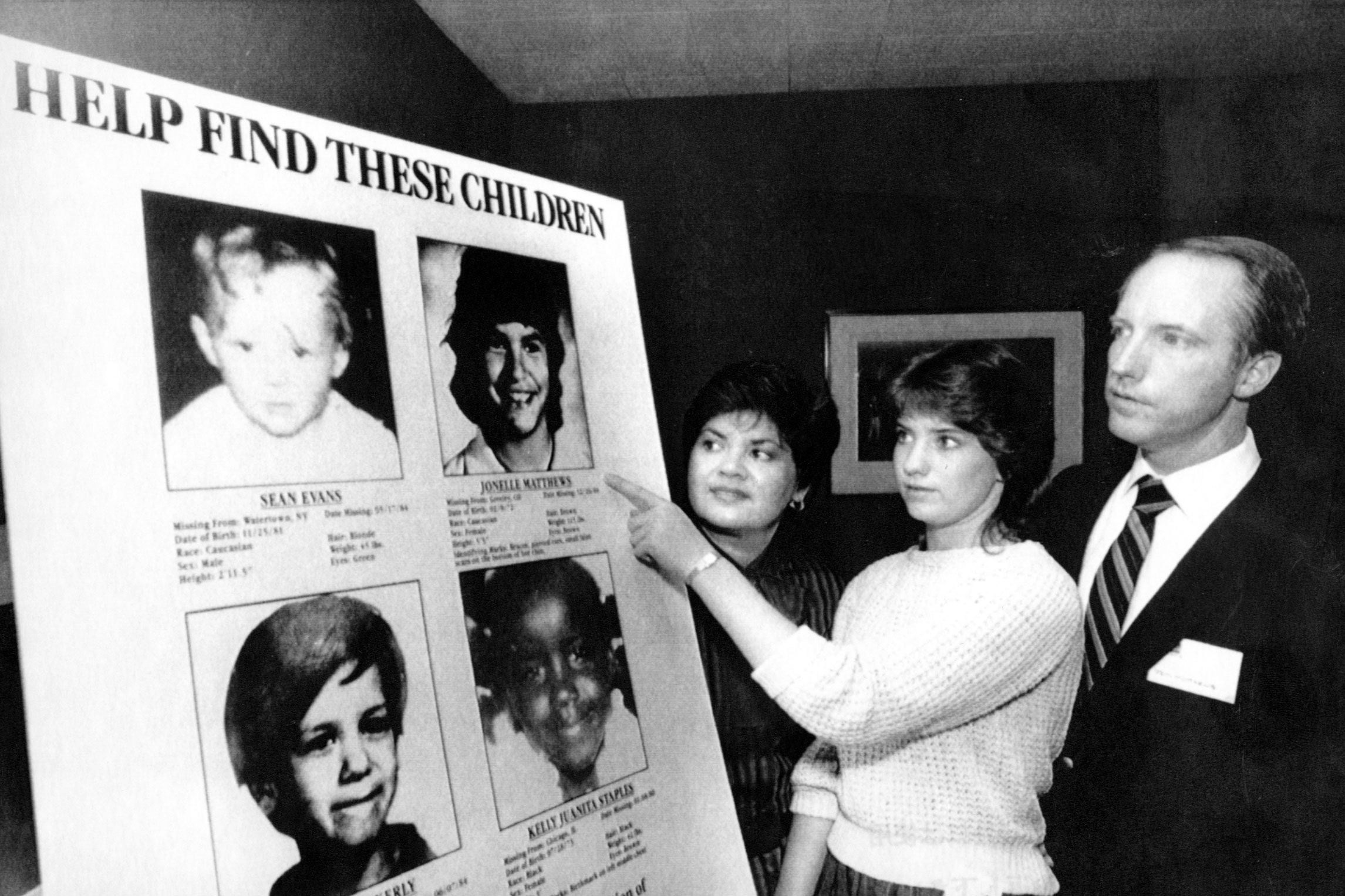 Jennifer Matthews, 16, points to a photo of her missing sister, Jonelle, 13, as parents Gloria and Jim Matthews, of Boulder, Colo., look on Friday April 19, 1985, in New York. Playhouse Video announced a poster program as part of a campaign to help locate missing children that it hopes will involve 24,000 nationwide video retail outlets and be seen by 144 million customers.