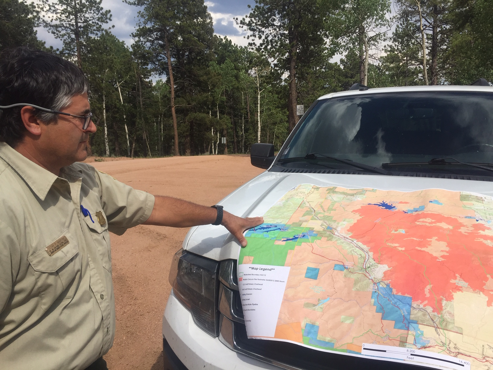 Oscar Martinez with the US Forest Service points to a map where water infrastructure and forested lands overlap