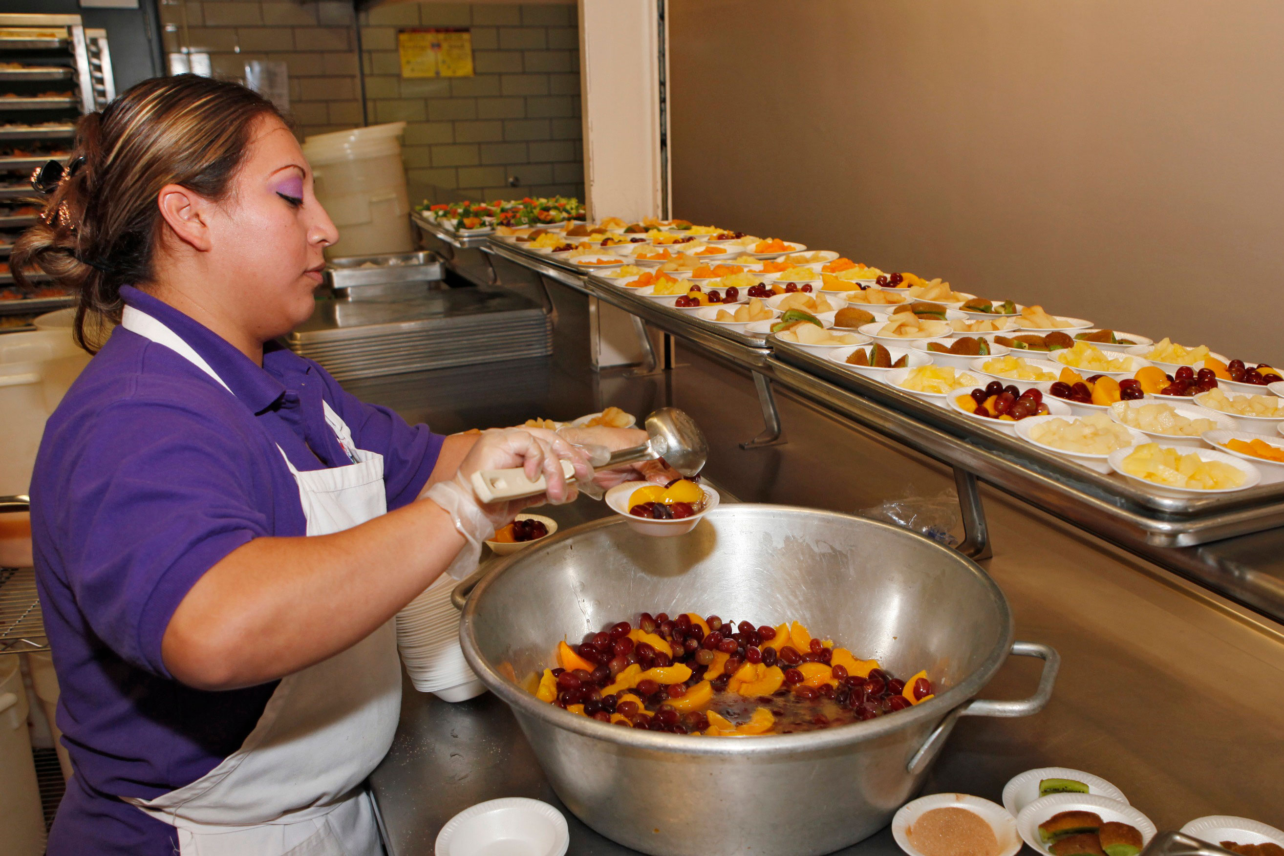 In this Jan.18, 2012 photo, Vivan Perez prepares bowls of fruit for lunch in the kitchen at Kepner Middle School in Denver.