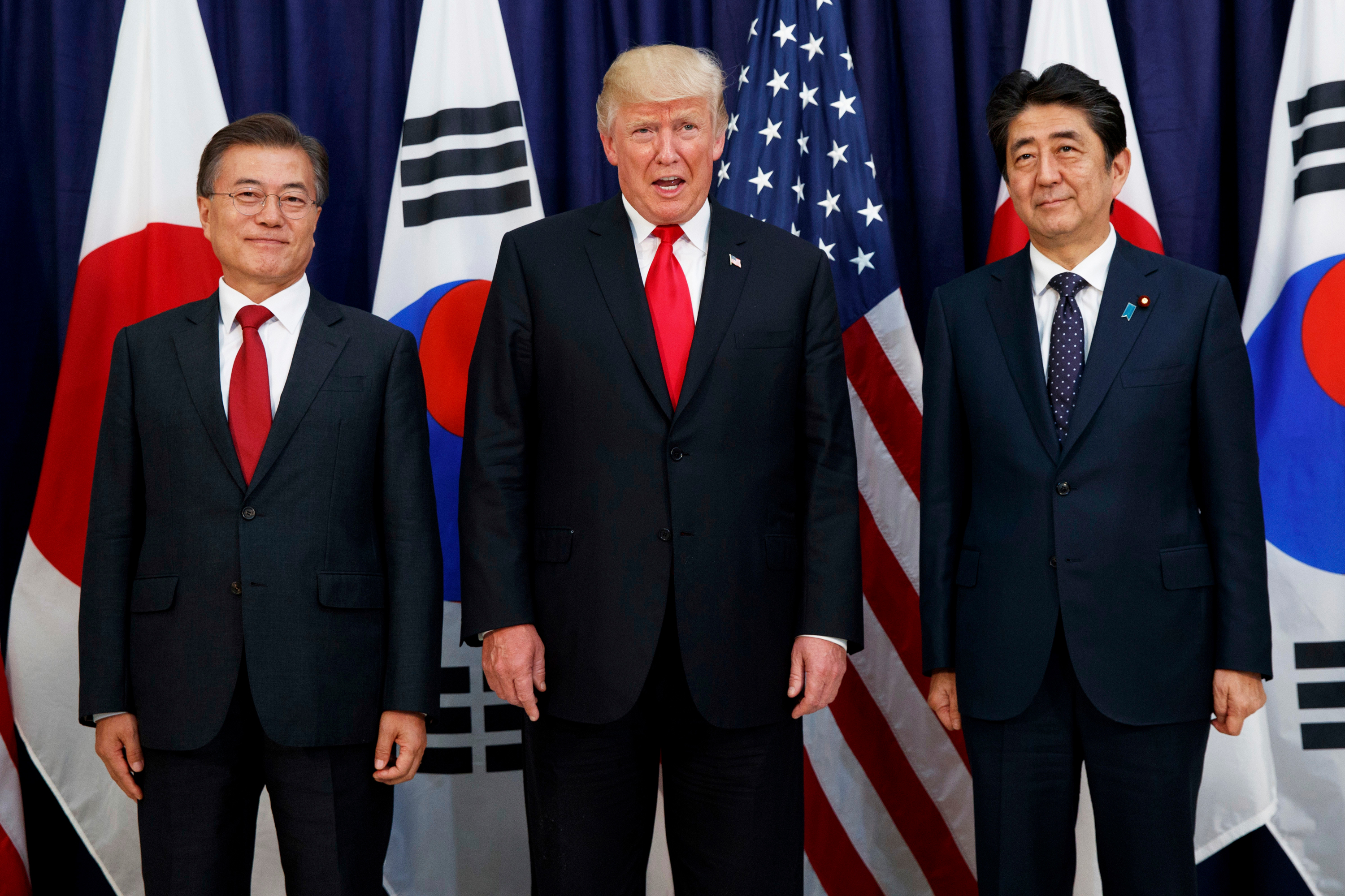 In this July 6, 2017, file photo, U.S. President Donald Trump, center, meets with Japanese Prime Minister Shinzo Abe, right, and South Korean President Moon Jae-in before the Northeast Asia Security dinner at the U.S. Consulate General Hamburg in Germany. In August 2019, Trump angered some Asian American voters after the New York Post reported that he mocked the accents of Moon and Abe at a fundraiser in the Hamptons.
