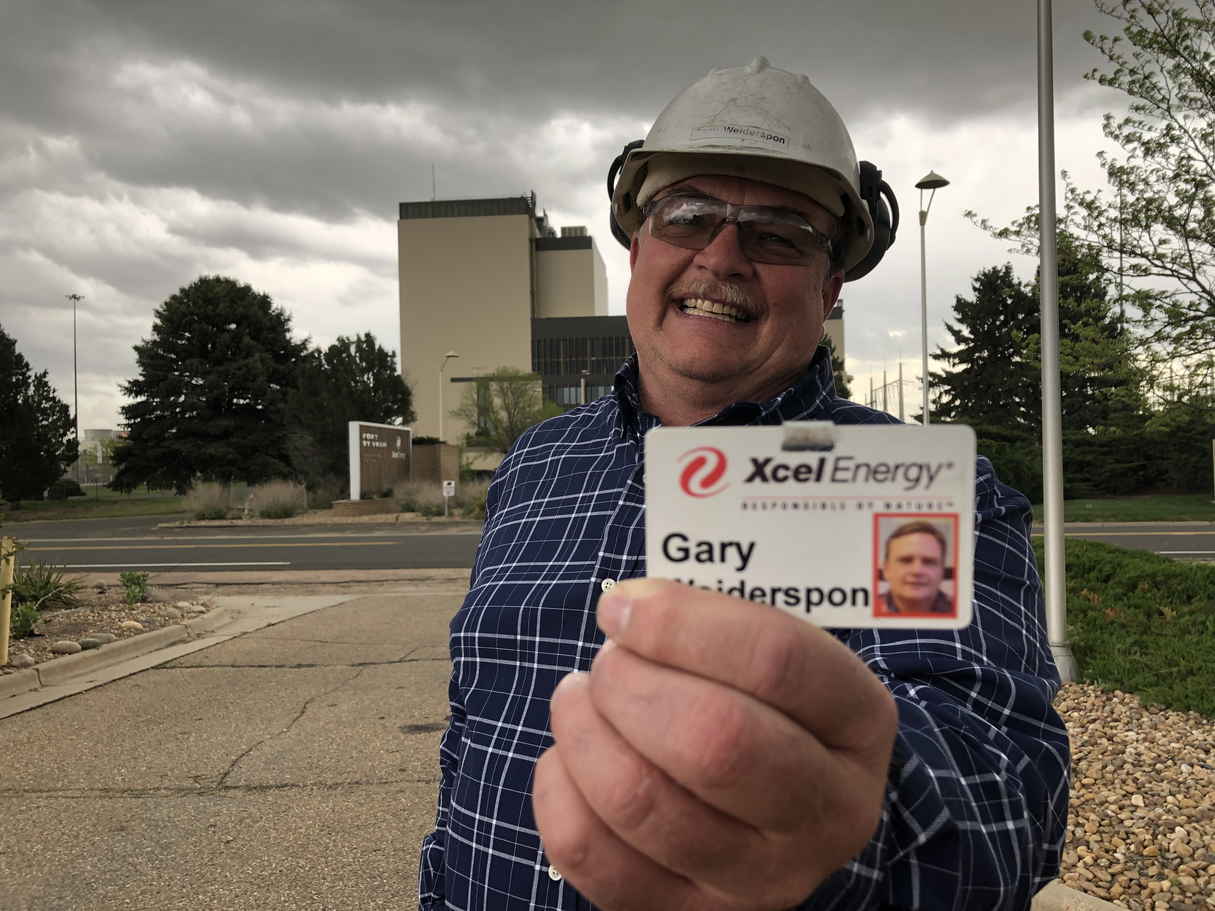 Gary Wiederspoon has worked at the former nuclear power plant, Fort St. Vrain since 1984. He shows off his name badge in front of the building in Platteville, Colo.