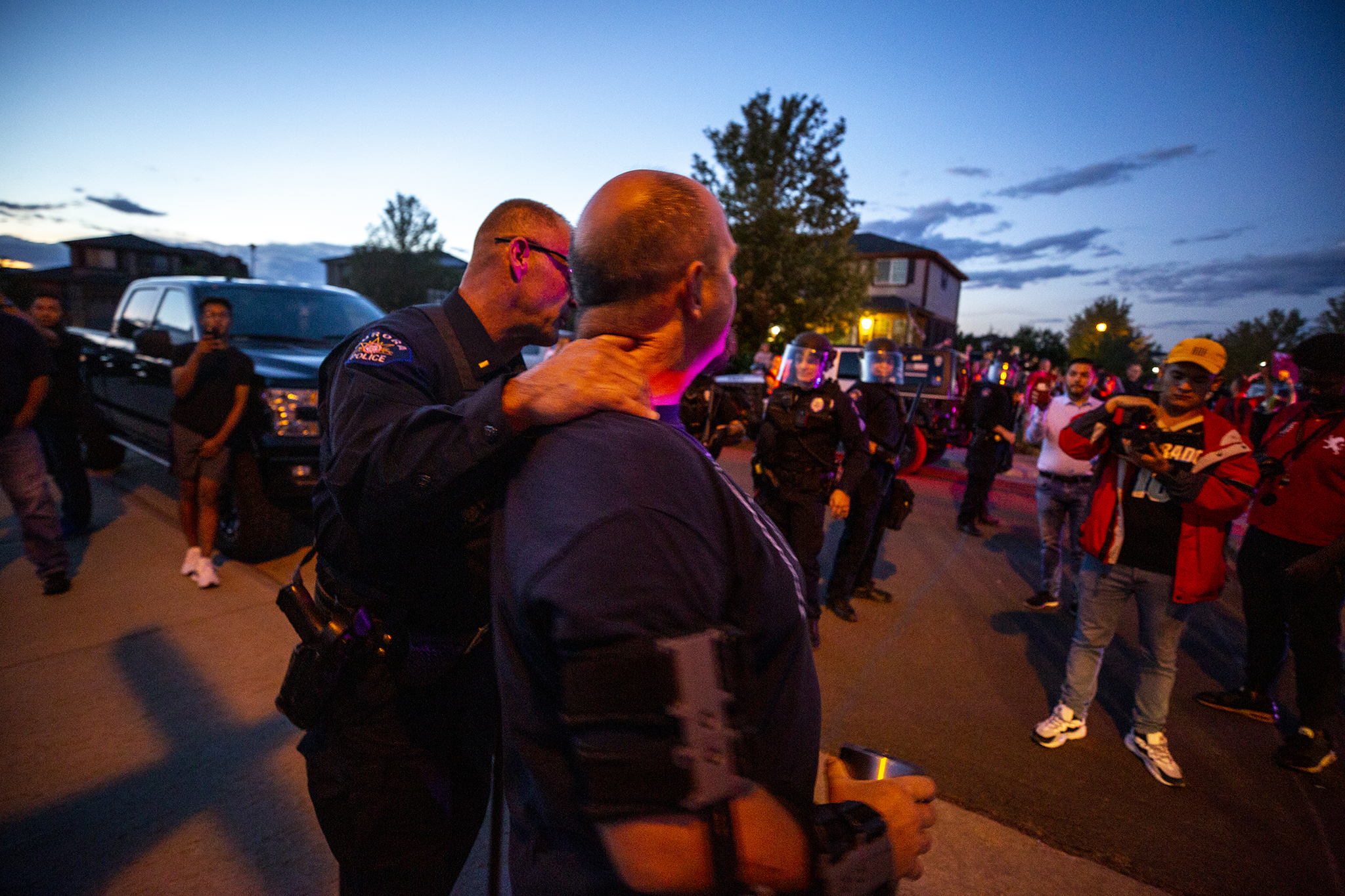 An Aurora Police officer pulls a counter protester away from immigration activists marching on the home of Johnny Choate, GEO Group's lead of their contract immigration jail in Aurora. Sept. 19, 2019. (Kevin J. Beaty/Denverite)
